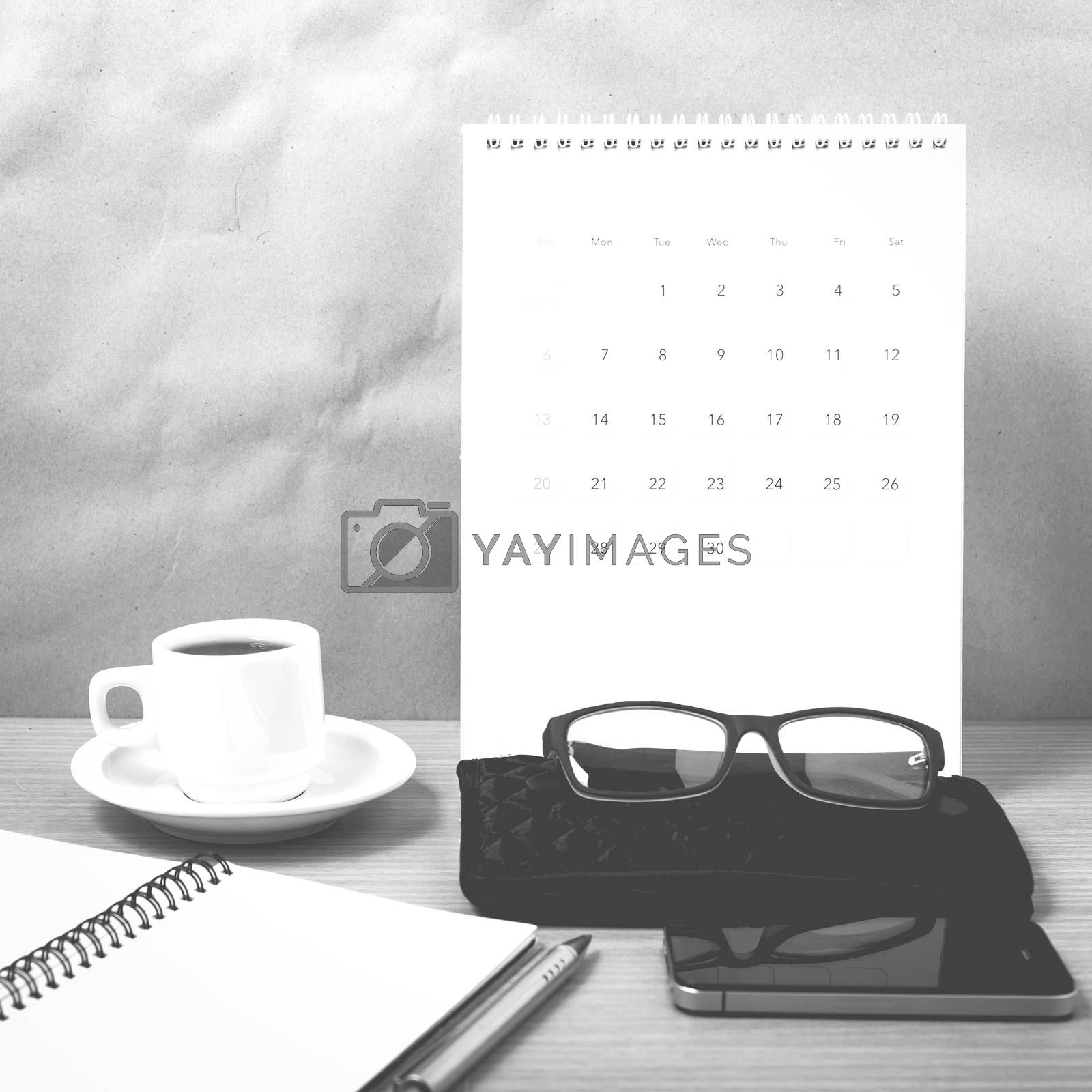 office desk : coffee with phone,calendar,wallet,notepad on wood background black and white color