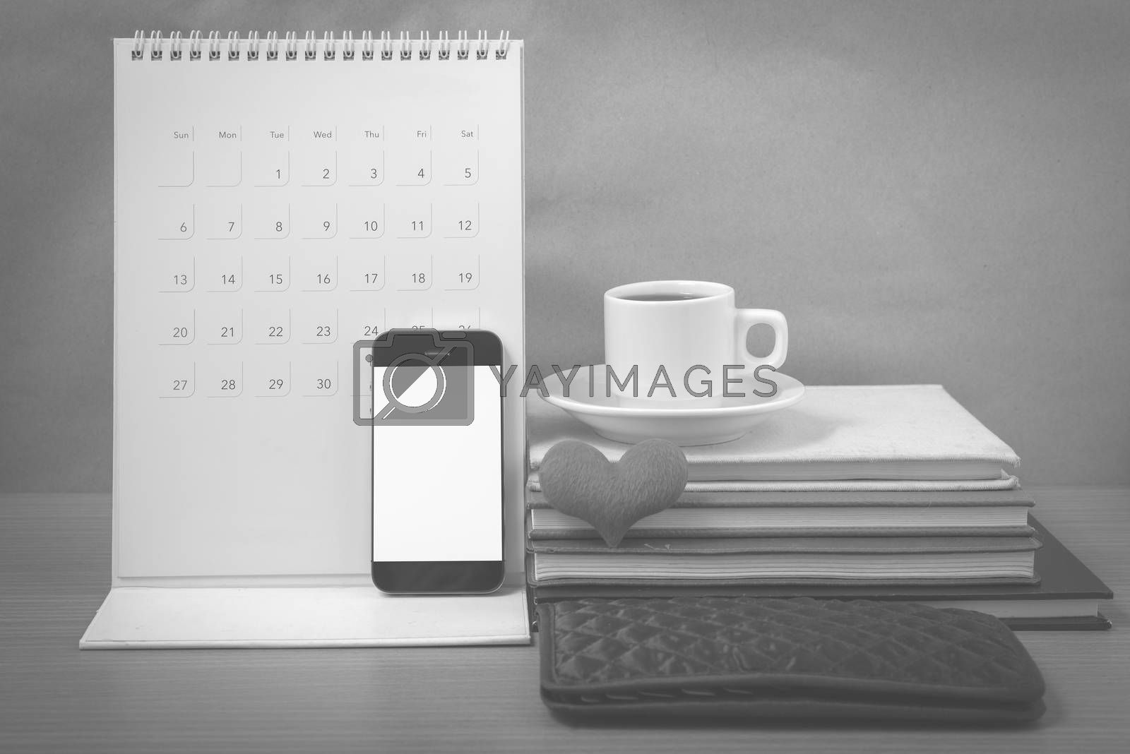 office desk : coffee with phone,wallet,calendar,heart,stack of book on wood background black and white color
