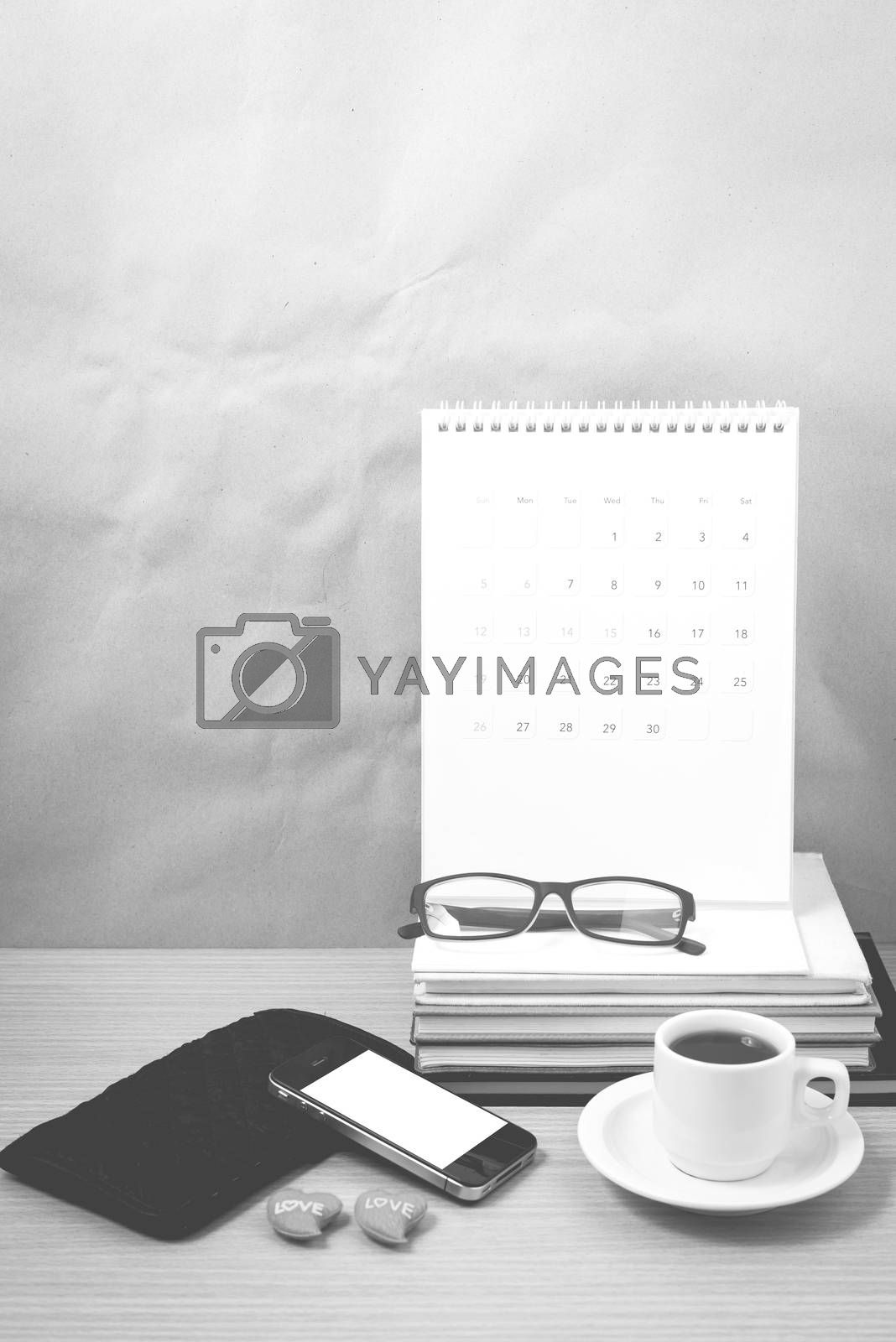 office desk : coffee with phone,wallet,calendar,heart,stack of book,eyeglasses on wood background black and white color