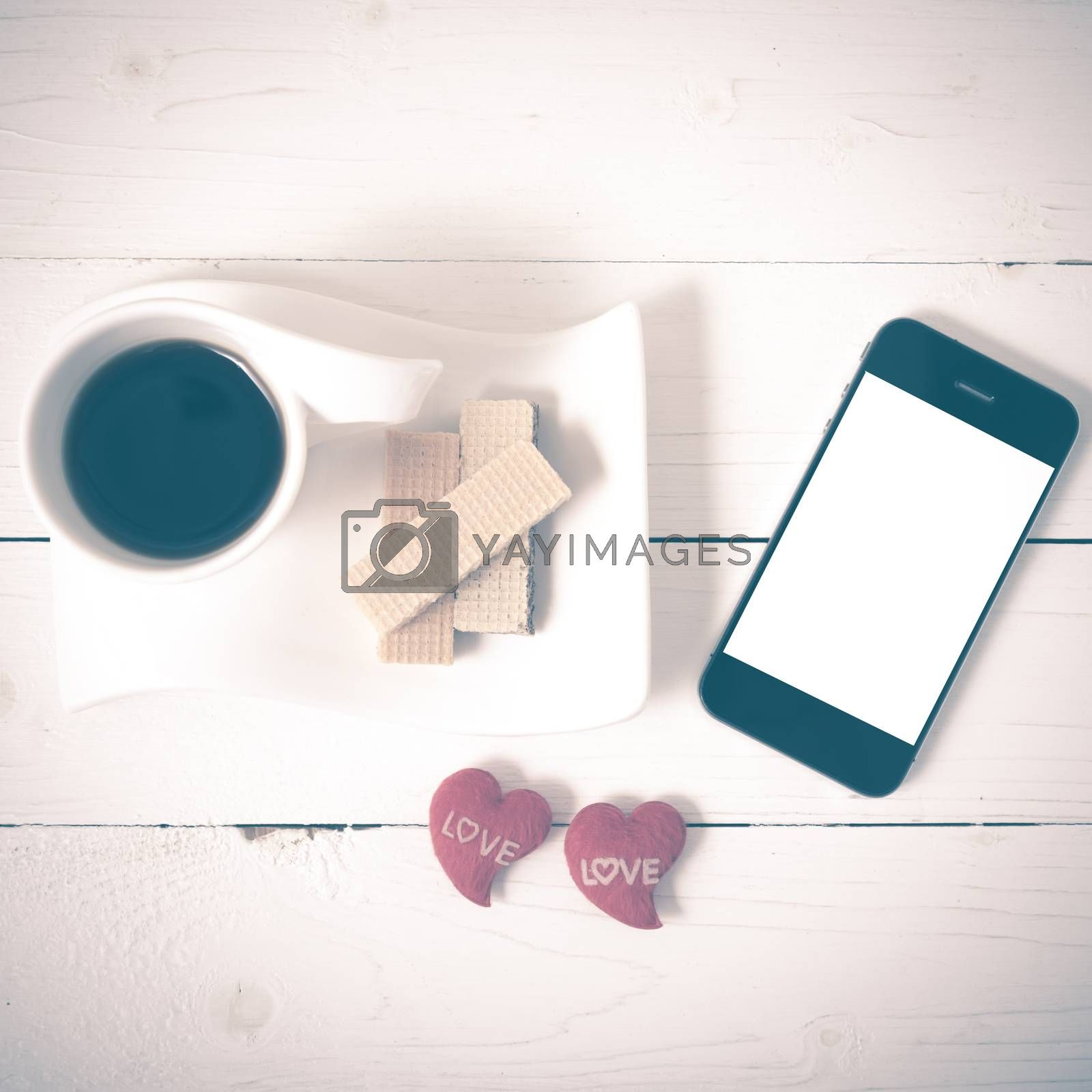 coffee cup with wafer,phone,heart on white wood background vintage style