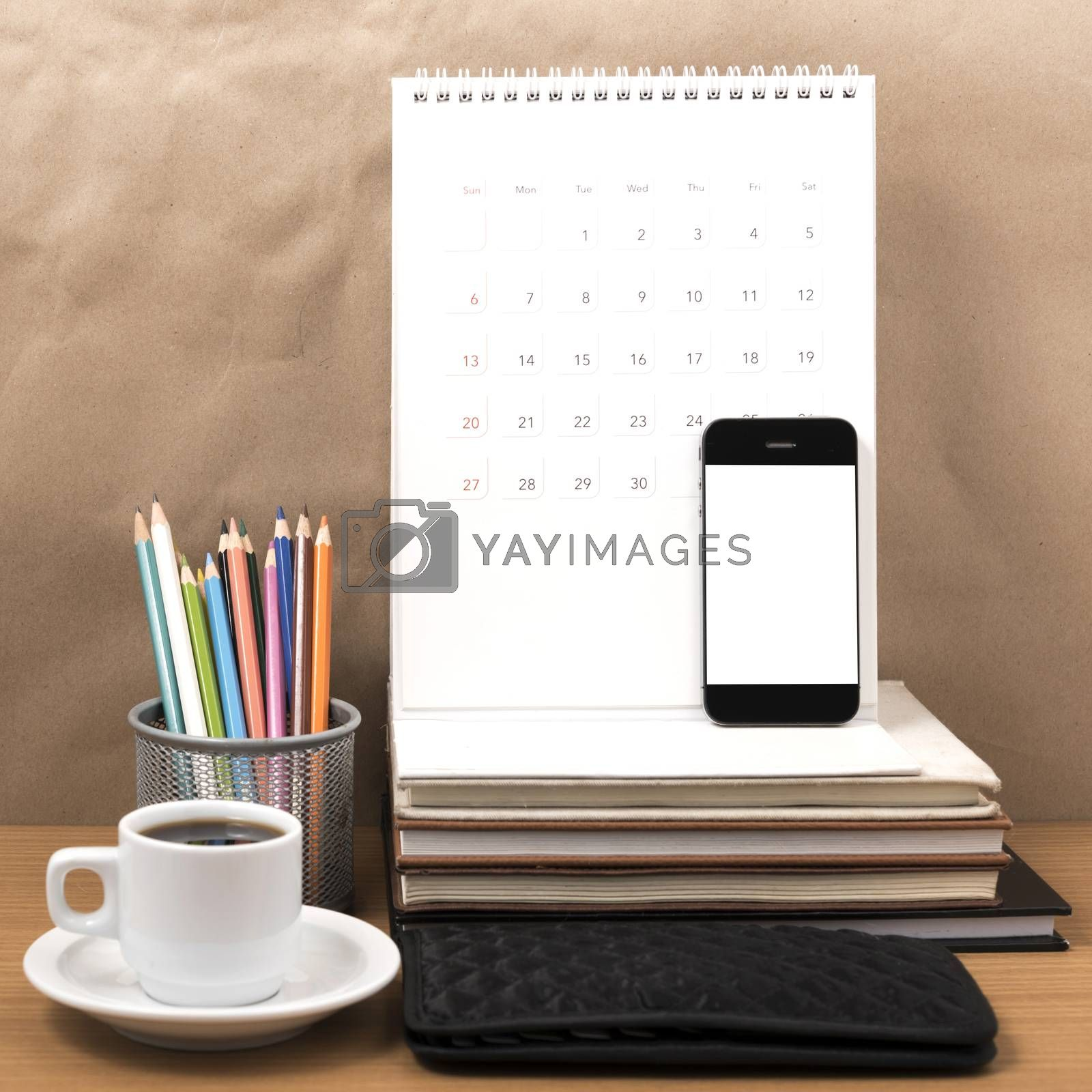 office desk : coffee with phone,wallet,calendar,color pencil box,stack of book on wood background