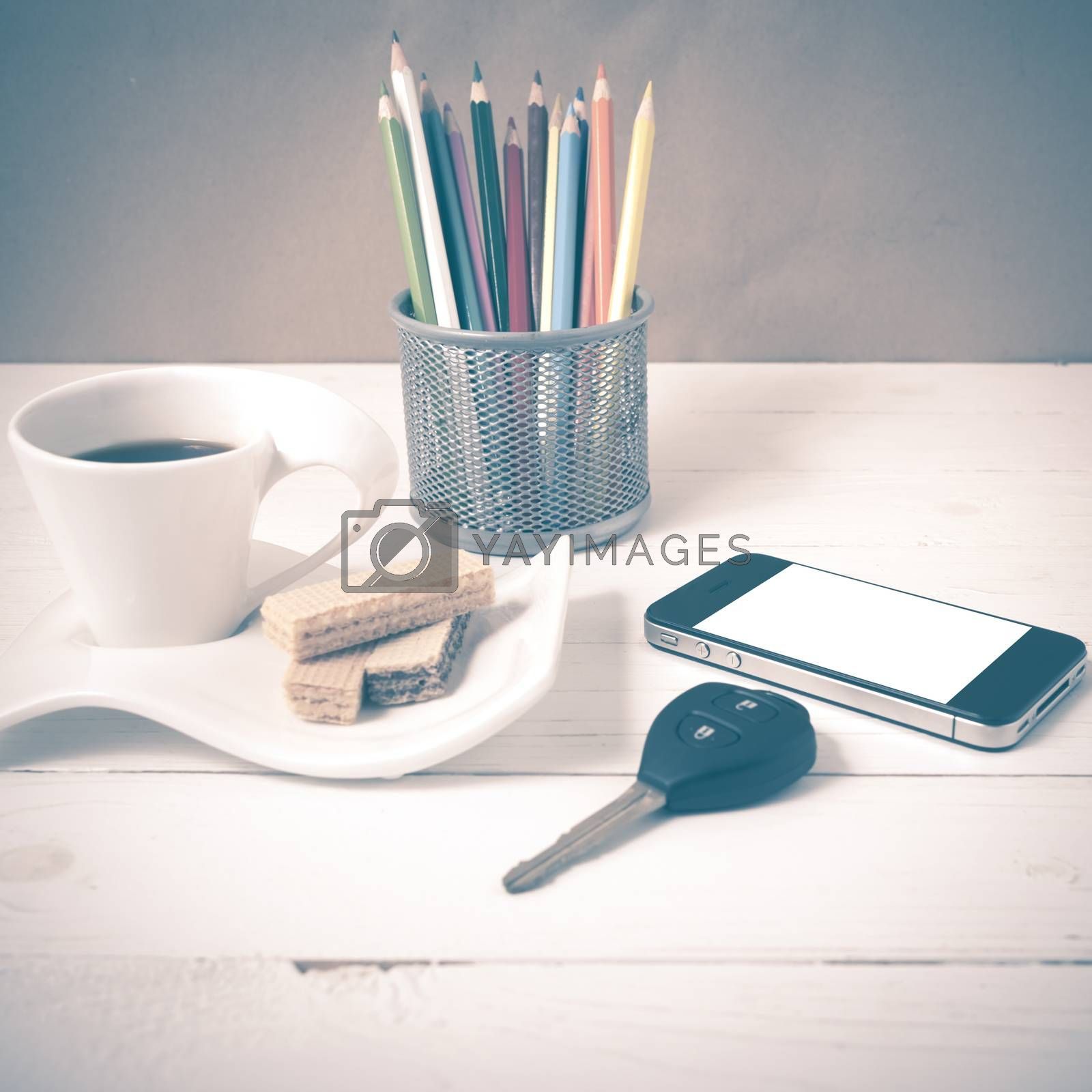coffee cup with wafer,phone,pencil box,car key on white wood background vintage style