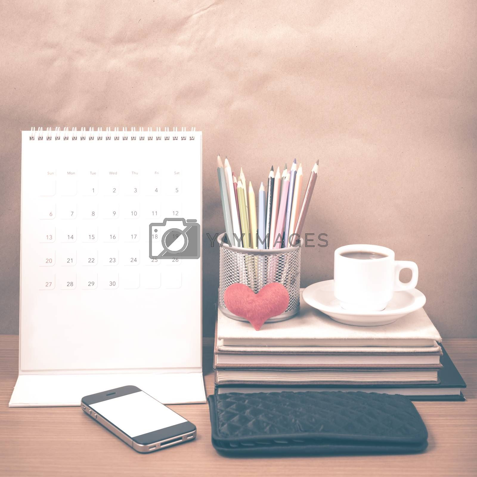 office desk : coffee with phone,wallet,calendar,heart,color pencil box,stack of book,heart on wood background vintage style