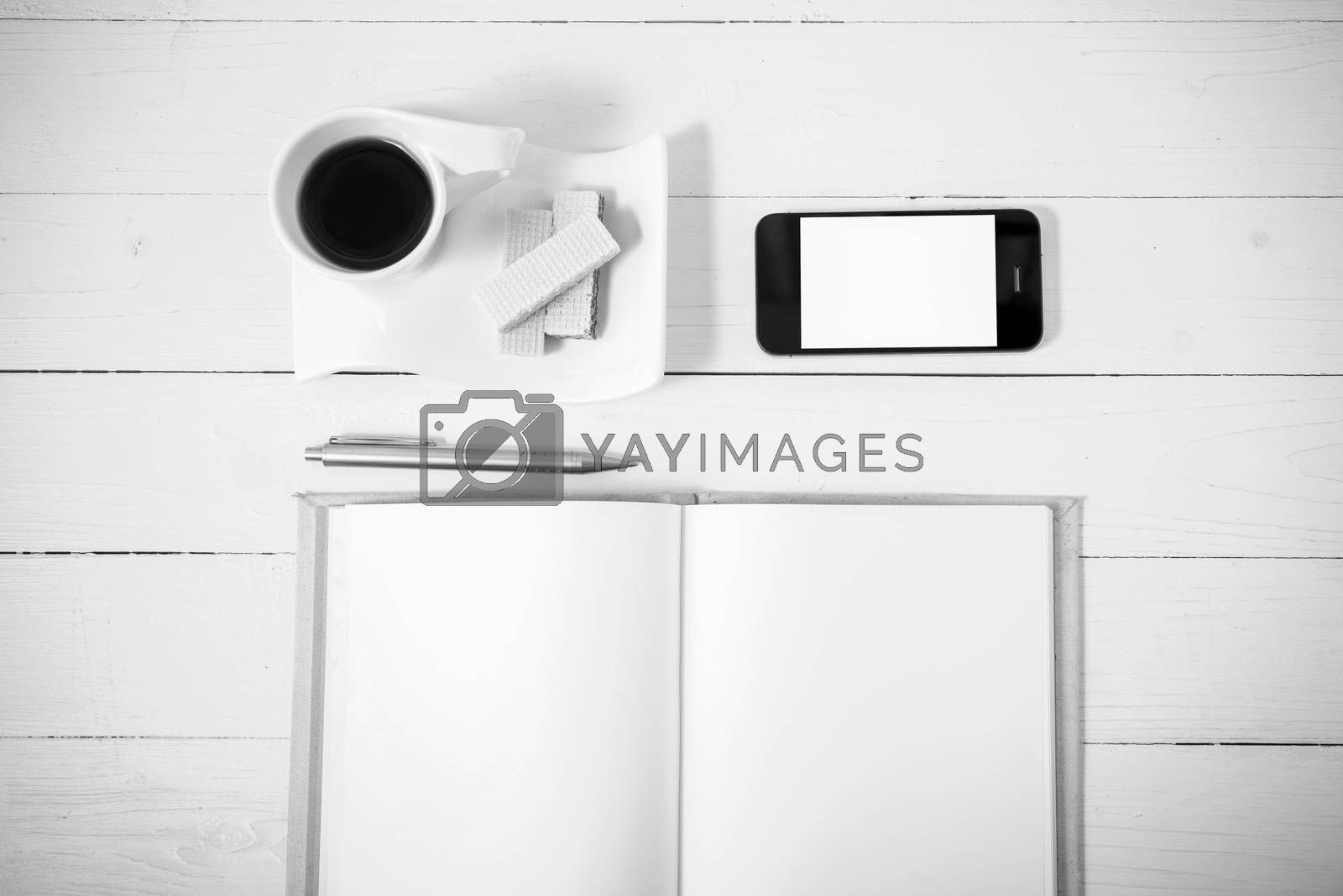 coffee cup with wafer,phone,notebook on white wood background black and white color