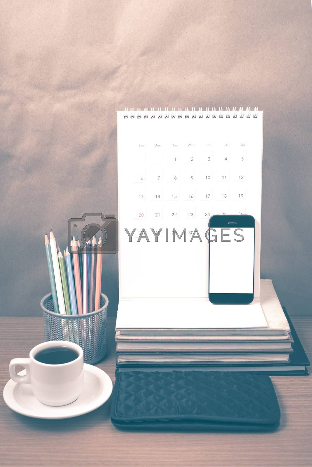 office desk : coffee with phone,wallet,calendar,color pencil box,stack of book on wood background vintage style