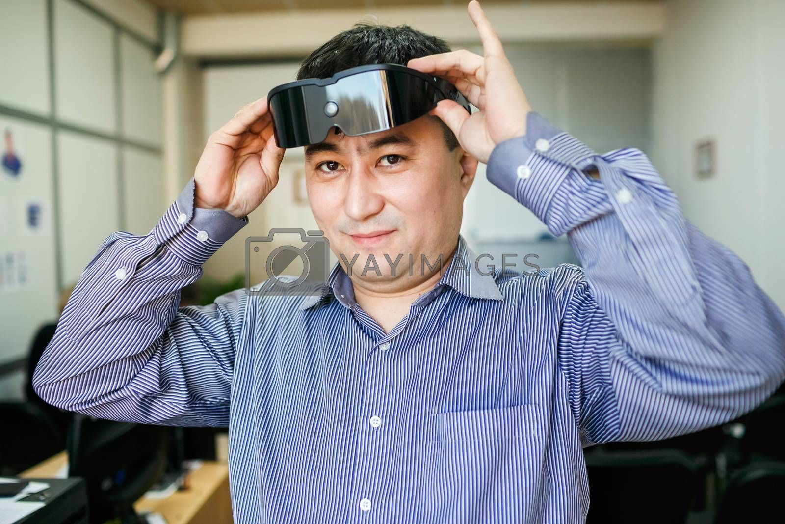 The man wears glasses virtual reality, inside the office.
