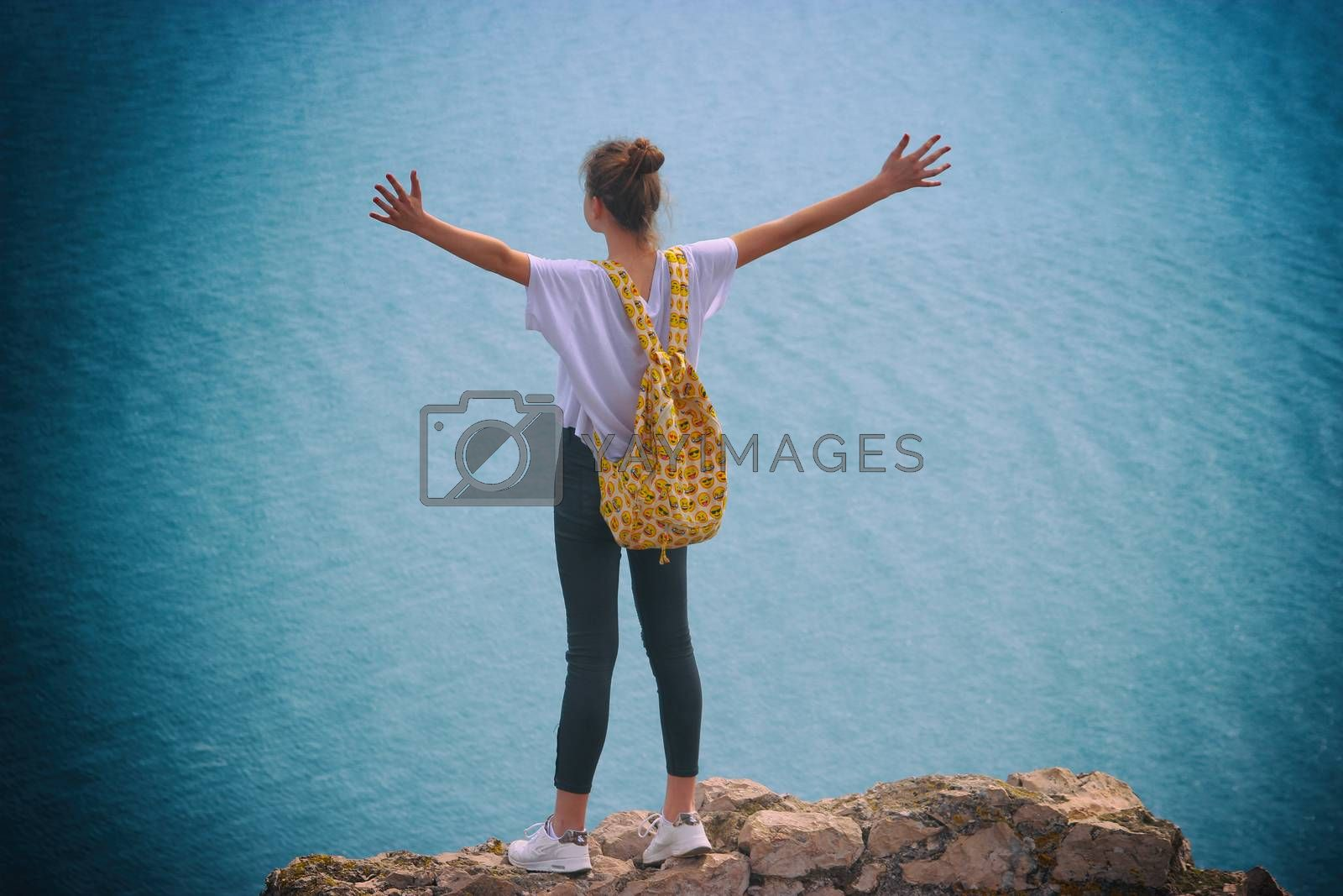 La Turbie, France - March 22, 2016: Freedom Concept. Free Happy Young Woman with a Backpack with Smileys Enjoying Nature. Mediterranean Sea in the Background