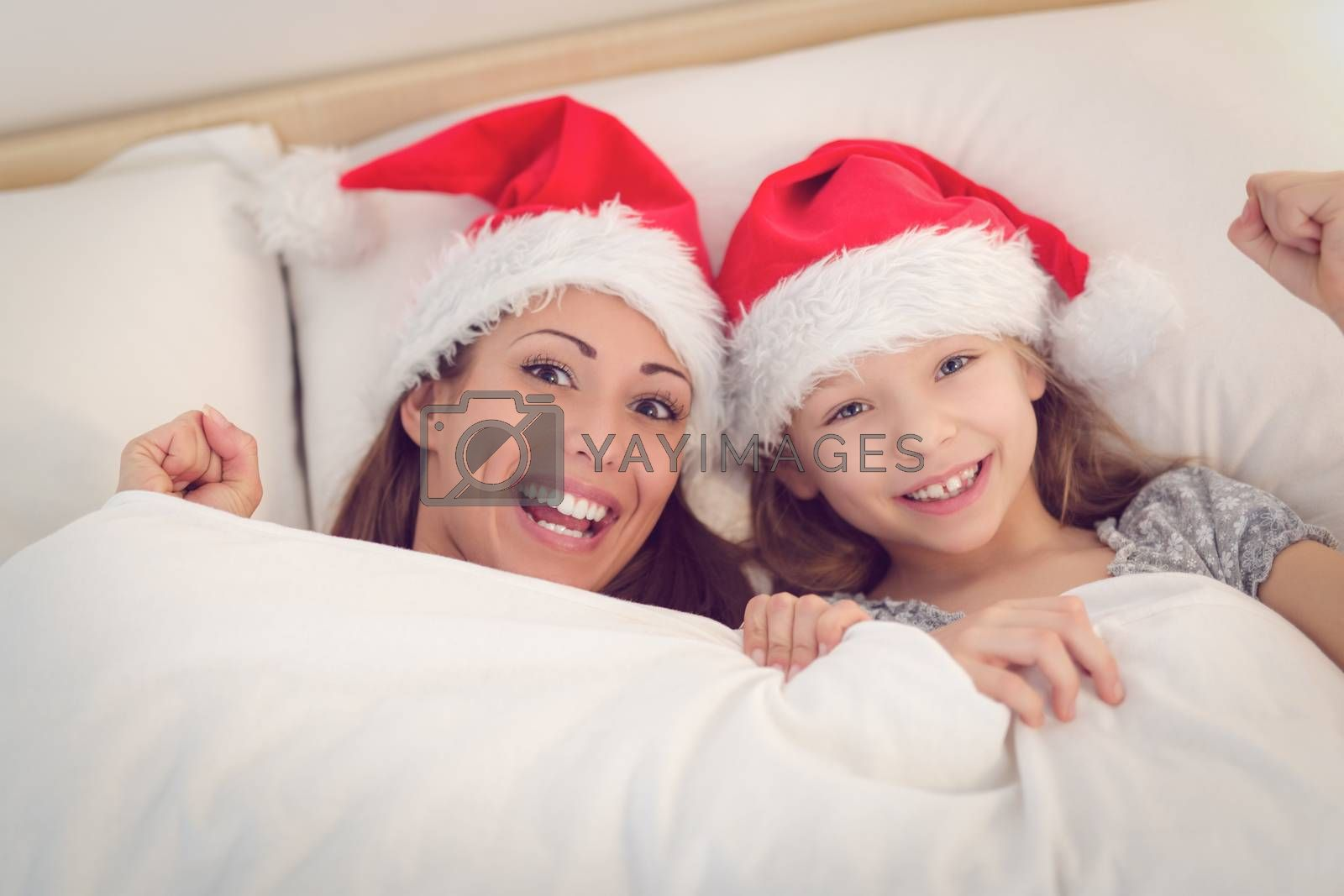 Beautiful smiling mother and her daughter with santa hat having fun in bed. They lie in bed looking at camera and peeking under the blanket with smile.