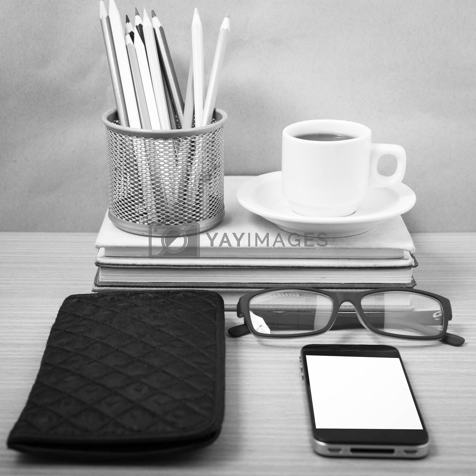 office desk : coffee with phone,stack of book,eyeglasses,wallet,color pencil box on wood background black and white color