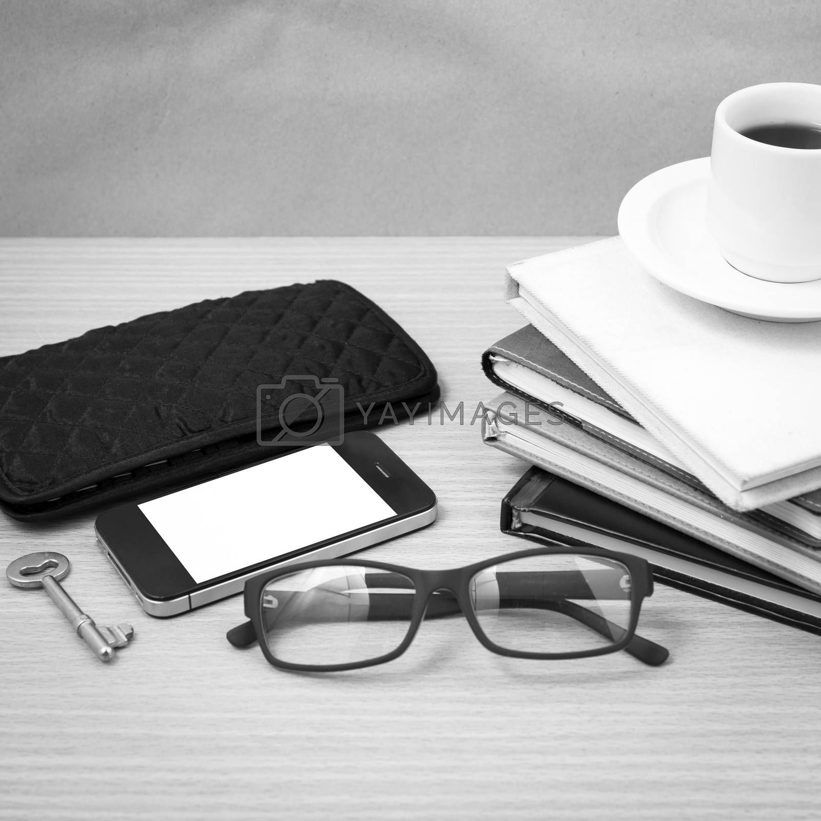 coffee and phone with stack of book,key,eyeglasses and wallet bl by Nisakorn Neera