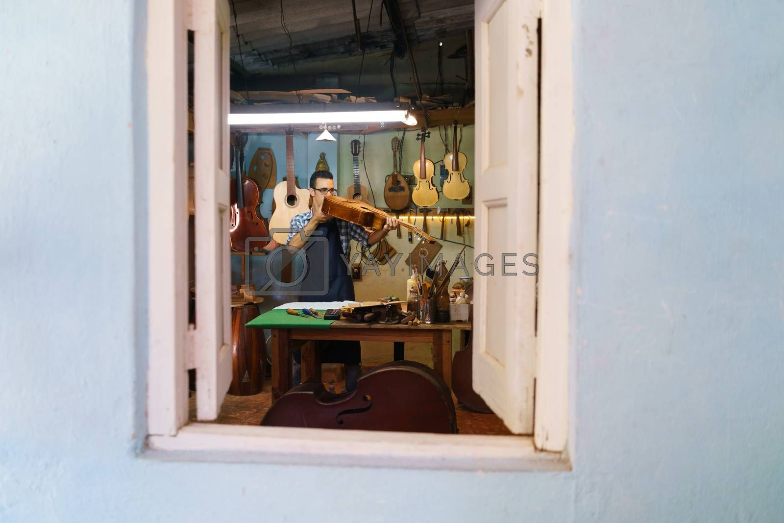 Lute maker shop and classic music instruments: young adult artisan fixing old classic guitar. The man looks carefully at bridge and arm to check the wood curvature. Full length