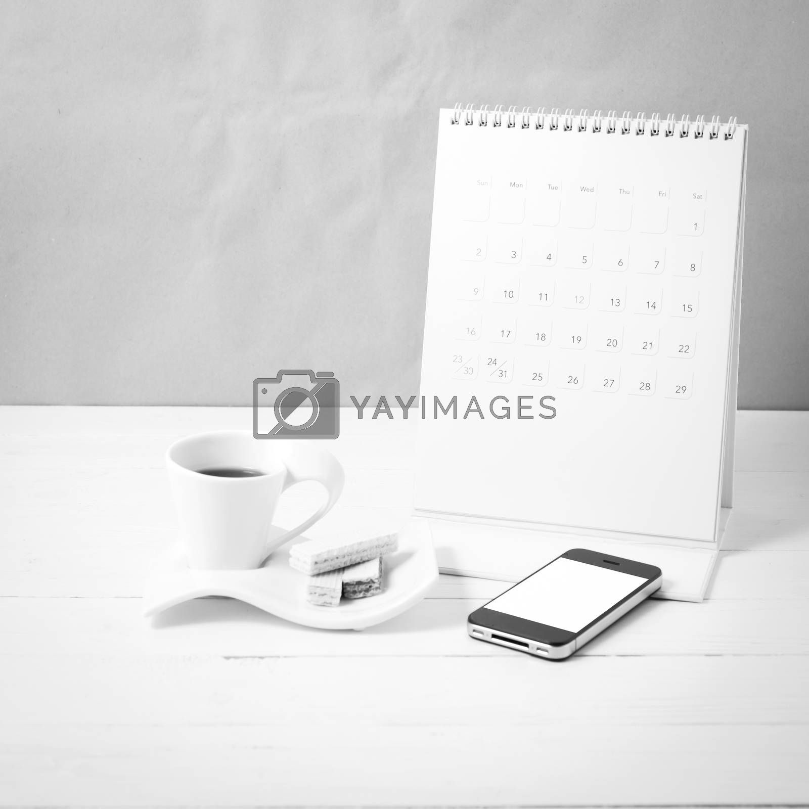 coffee cup with wafer,phone,calendar on white wood background black and white color
