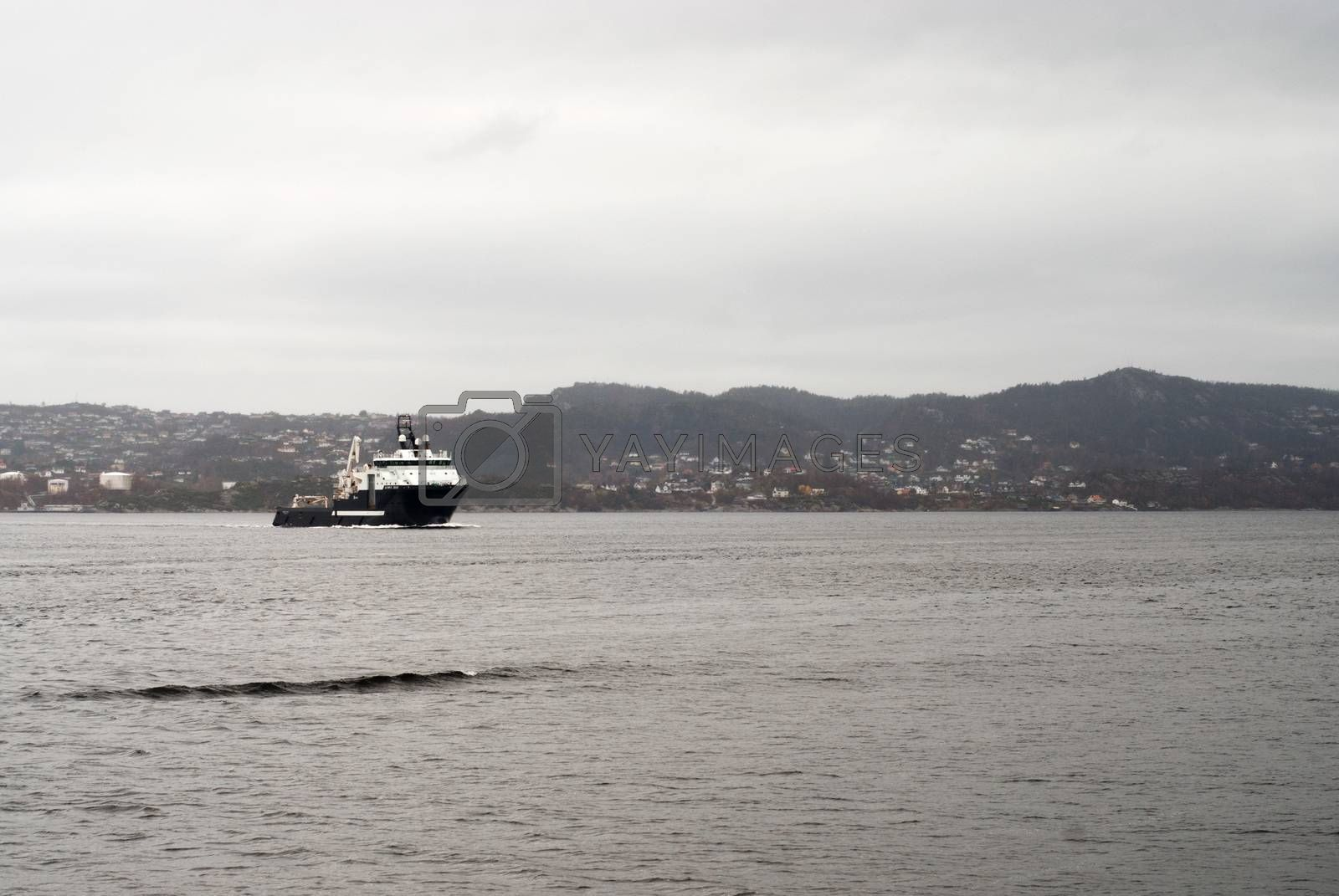 Cargo vessel is coming to port of Bergen, Norway