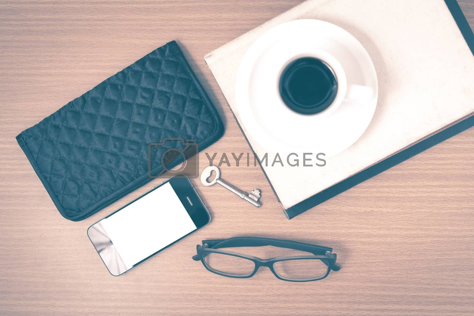 coffee and phone with stack of book,key,eyeglasses and wallet on wood background vintage style