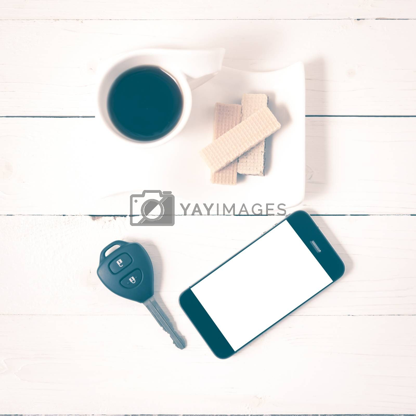 coffee cup with wafer,phone,car key on white wood background vintage style
