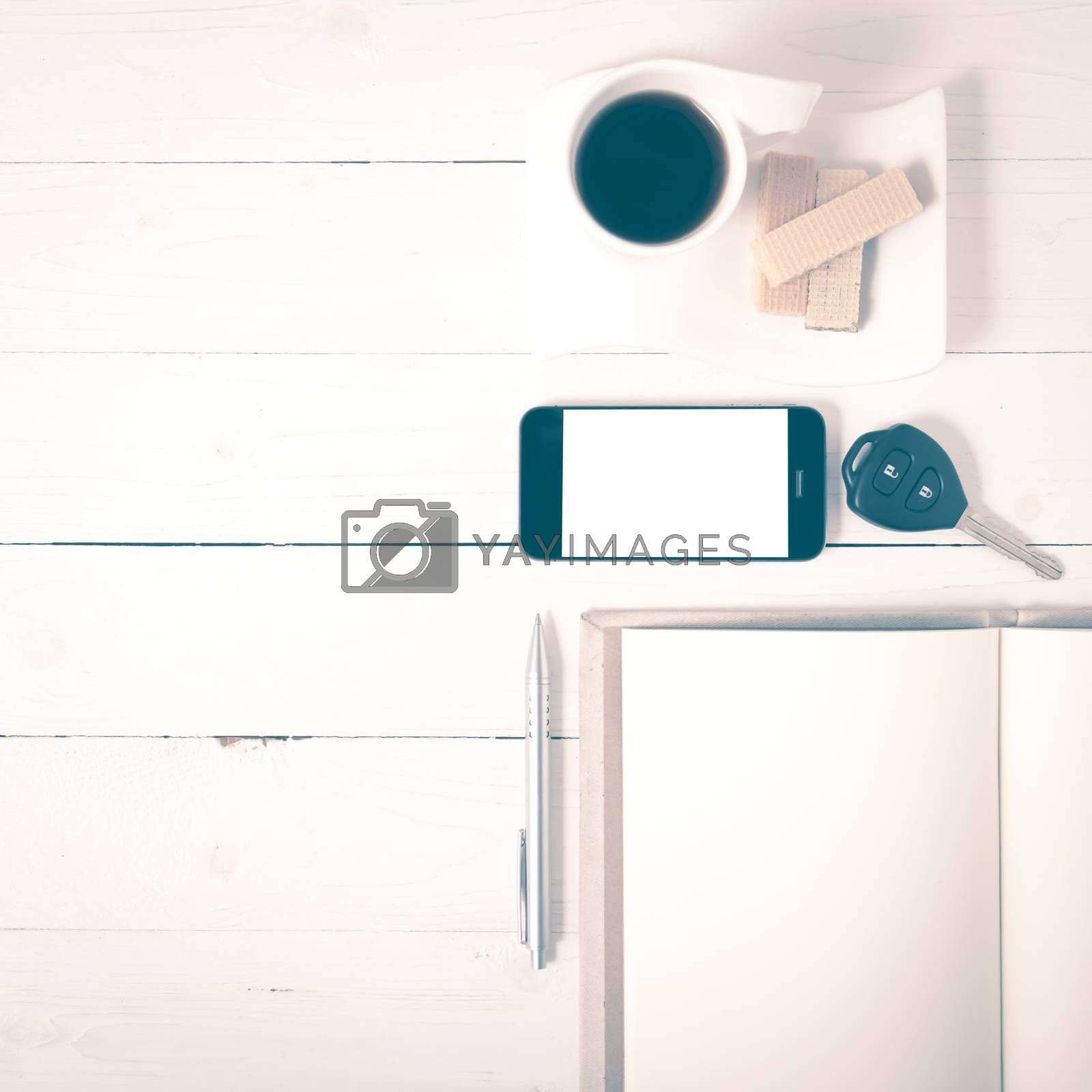 coffee cup with wafer,phone,car key,notebook on white wood background vintage style