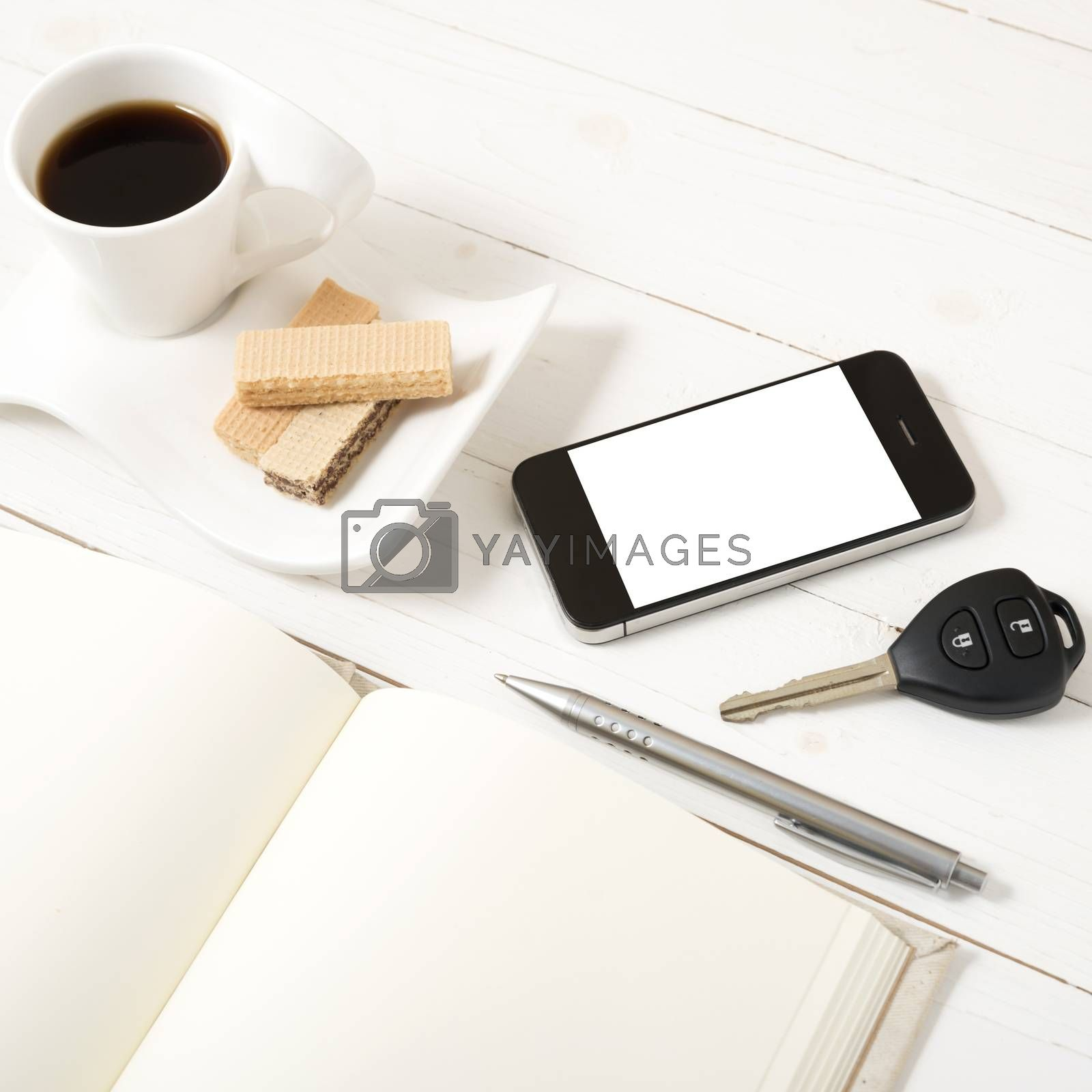 coffee cup with wafer,phone,car key,notebook on white wood background
