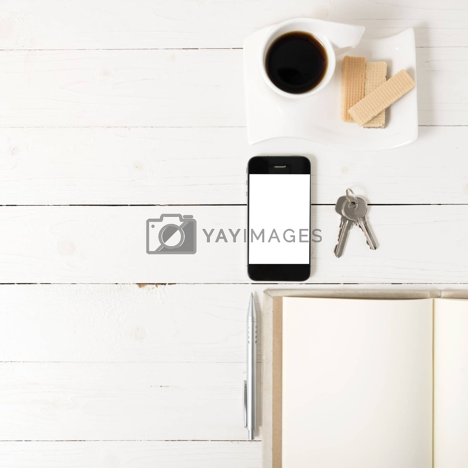 coffee cup with wafer,phone,key,notebook on white wood background