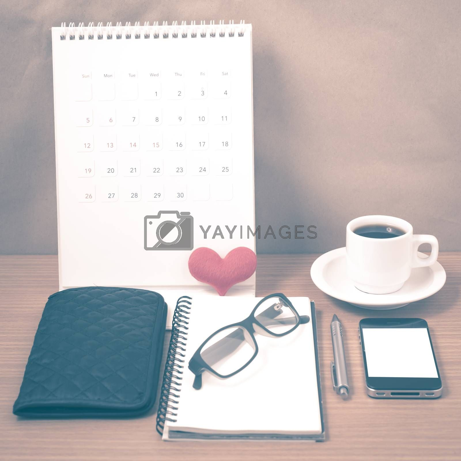 office desk : coffee with phone,wallet,calendar,heart,notepad,eyeglasses,heart on wood background vintage style