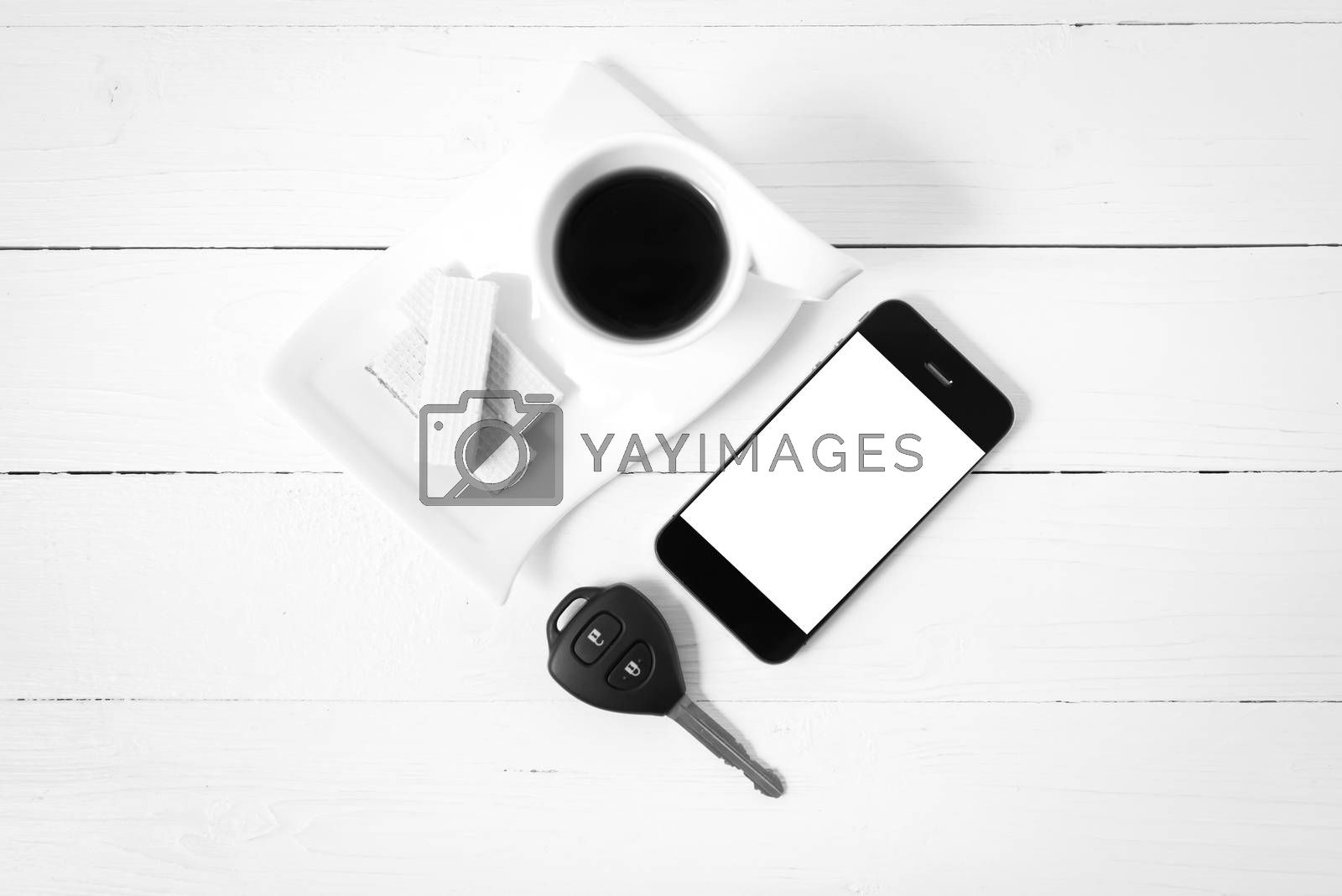 coffee cup with wafer,phone,car key on white wood background black and white color