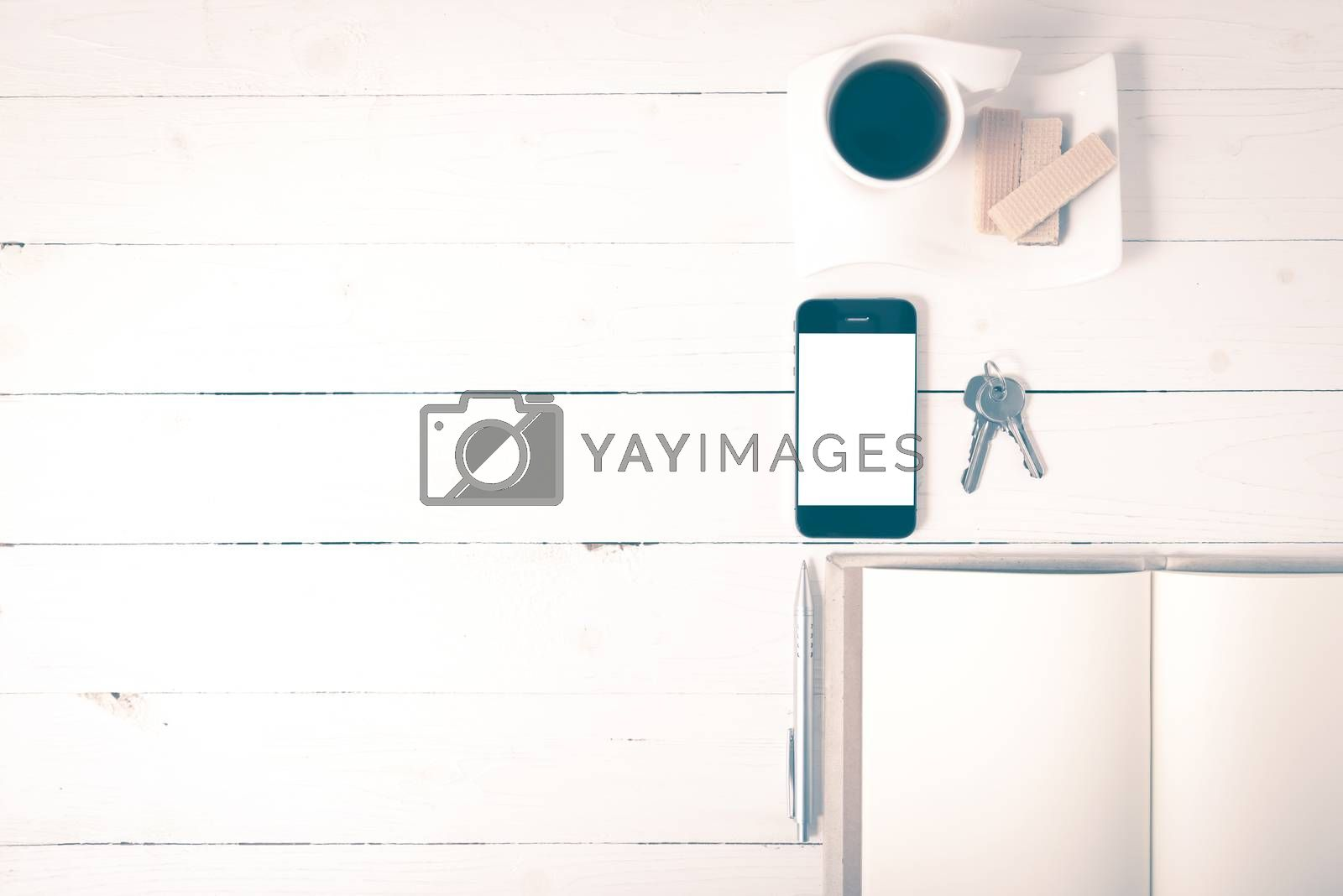 coffee cup with wafer,phone,key,notebook on white wood background vintage style