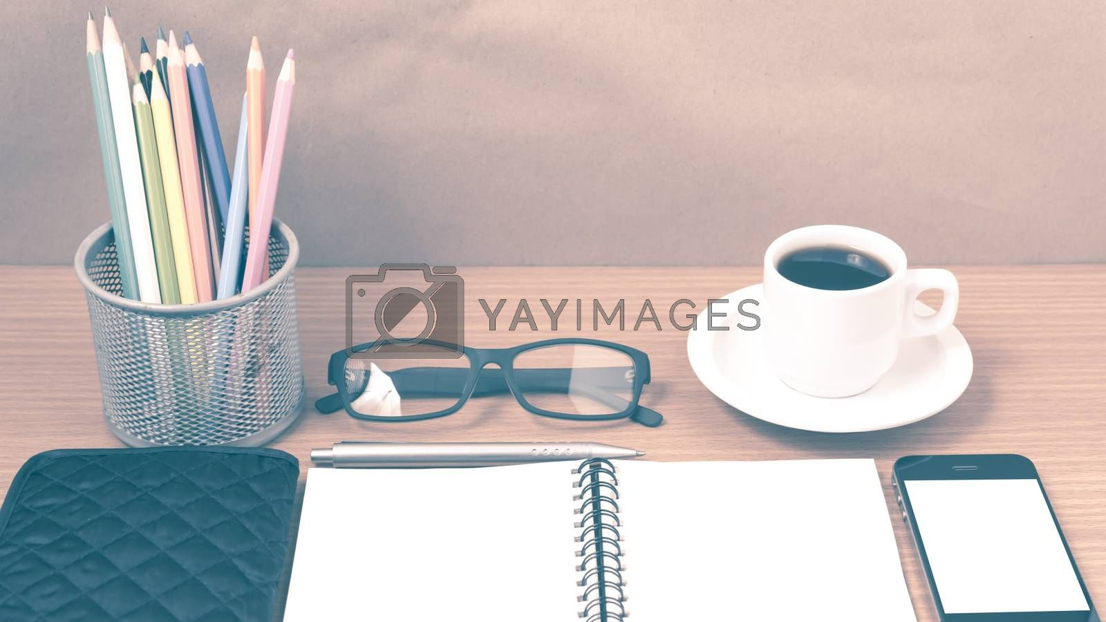office desk : coffee with phone,notepad,eyeglasses,wallet,color pencil box on wood background vintage style