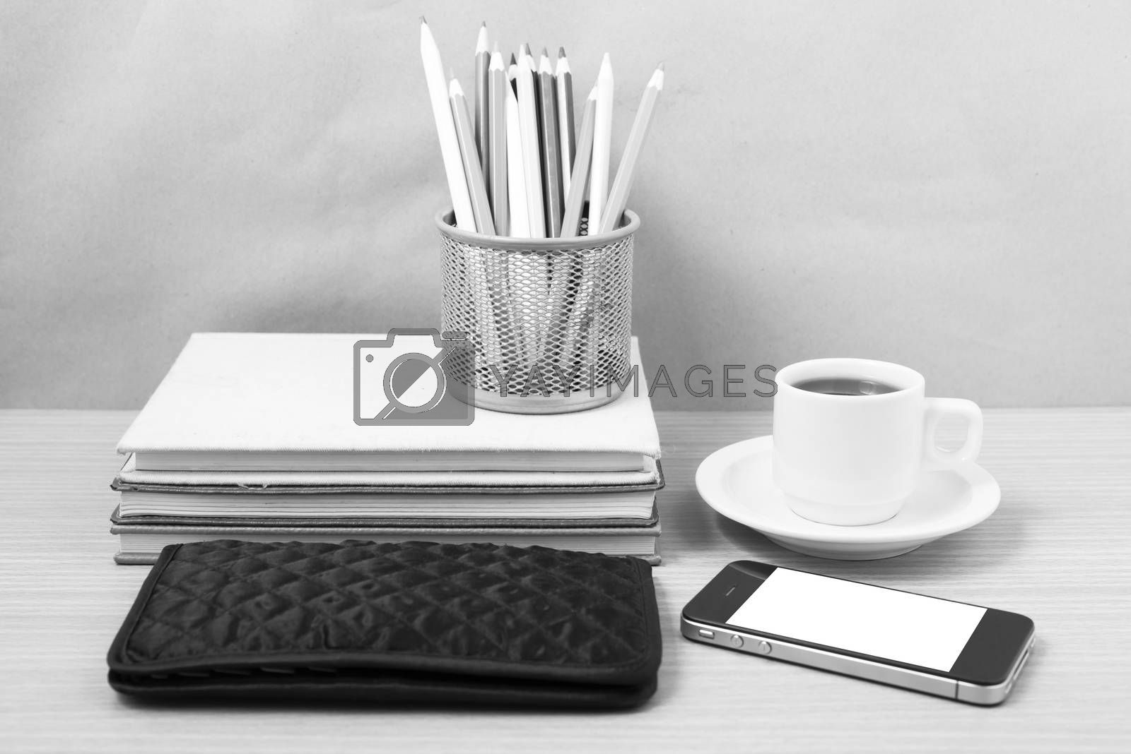 office desk : coffee with phone,stack of book,wallet,color box on wood background black and white color