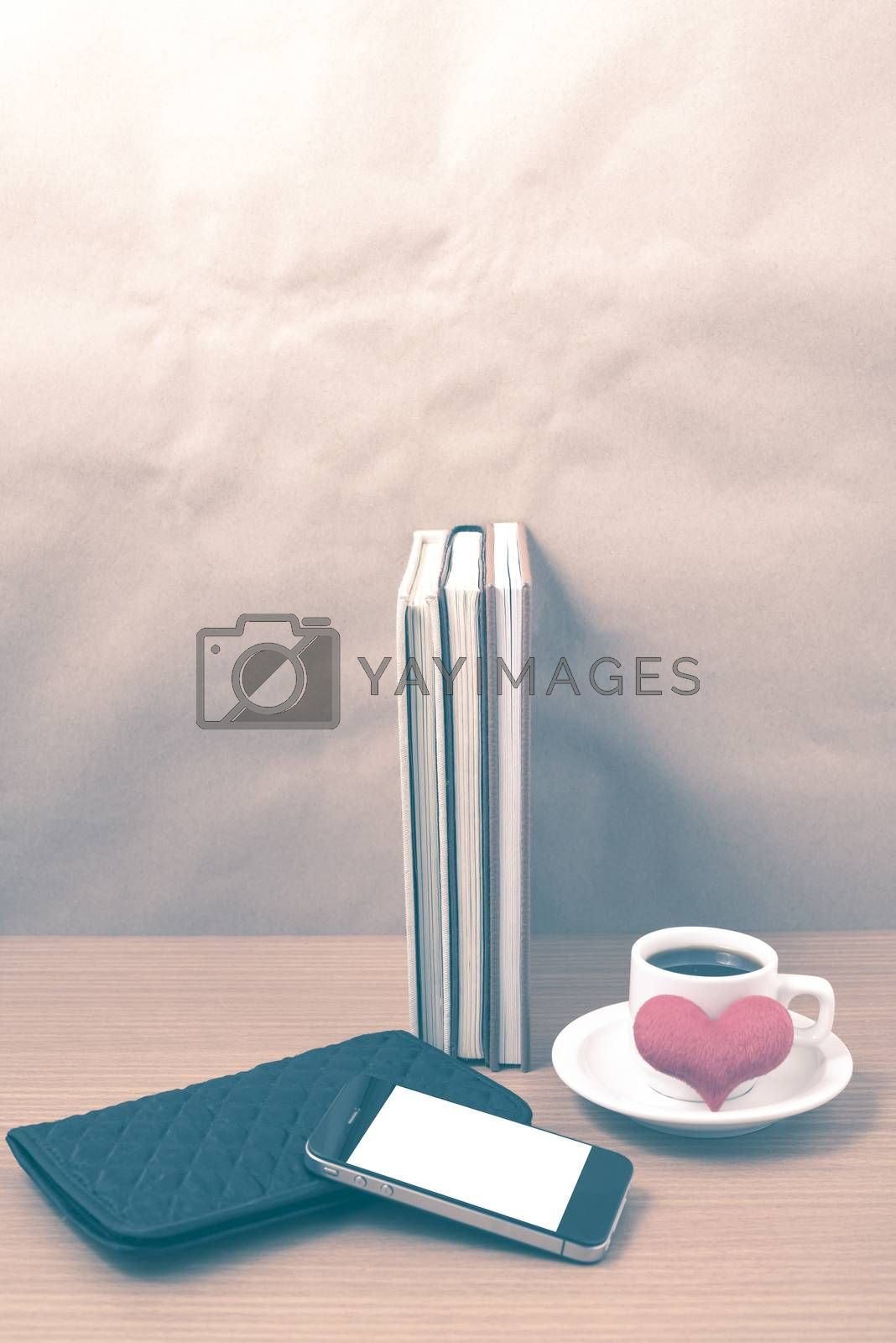 working table : coffee with phone,stack of book,wallet and heart on wood background vintage style