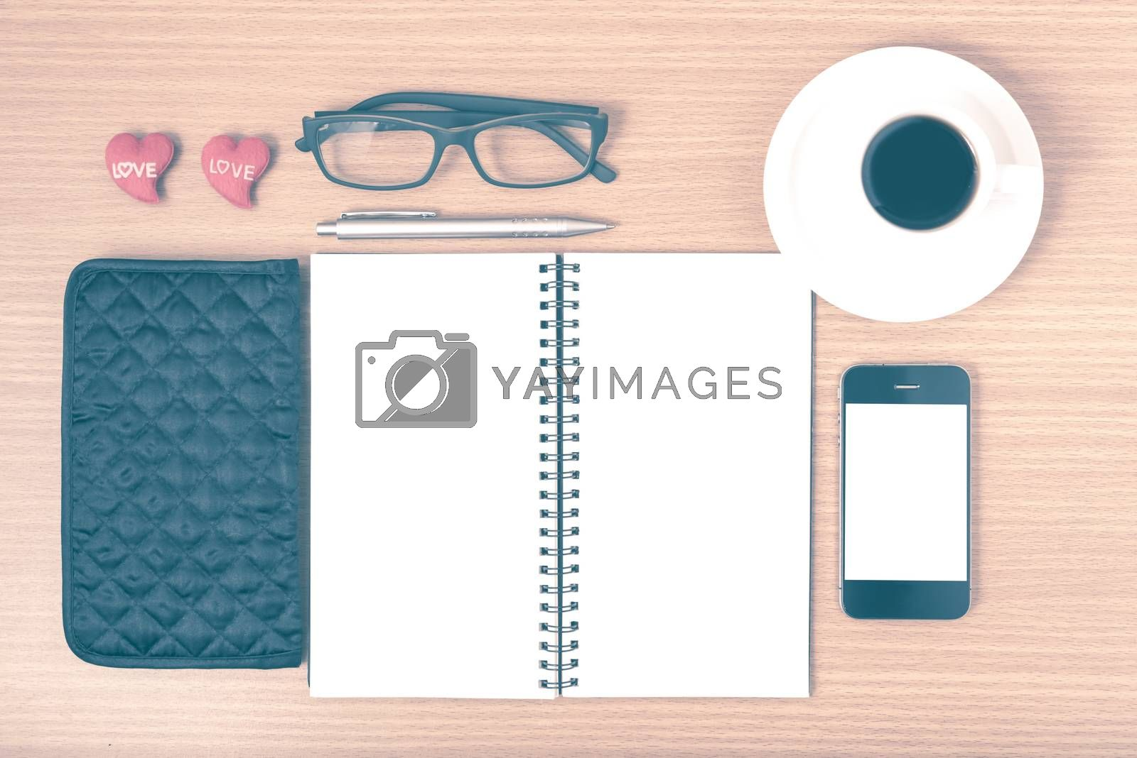office desk : coffee with phone,notepad,eyeglasses,wallet,heart on wood background vintage style