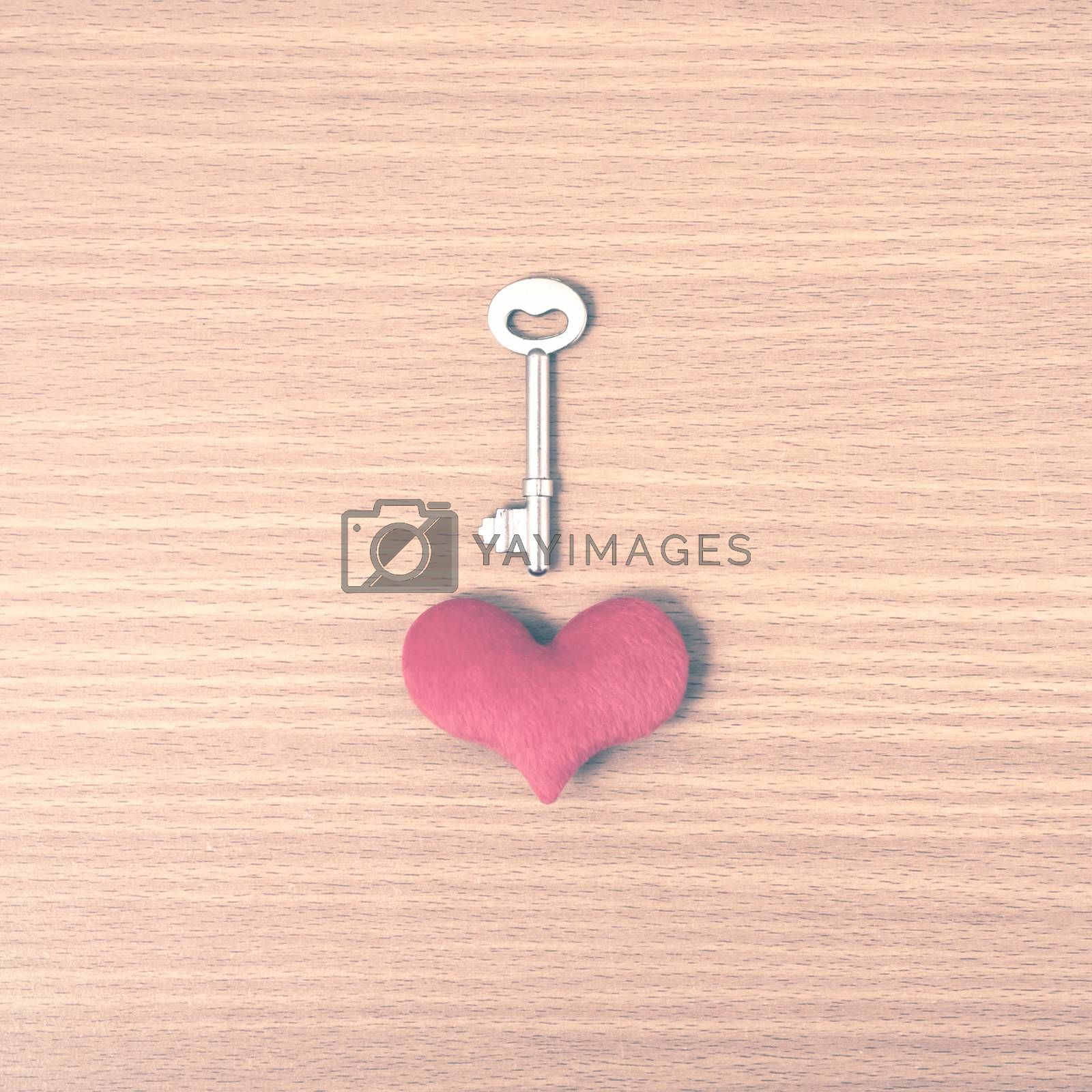 red heart with key on wood table background vintage style