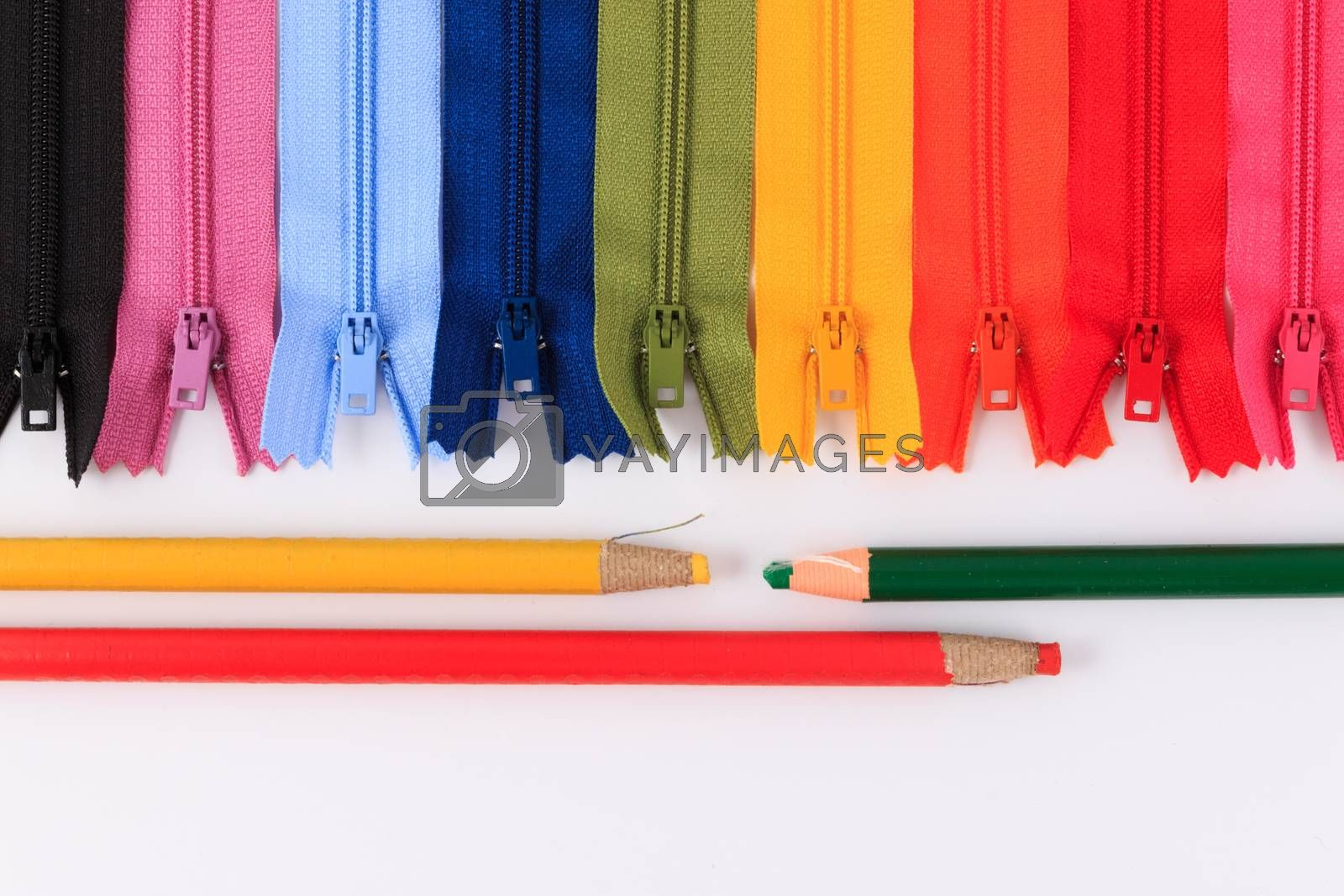Colorful zippers and pencils on white background.
