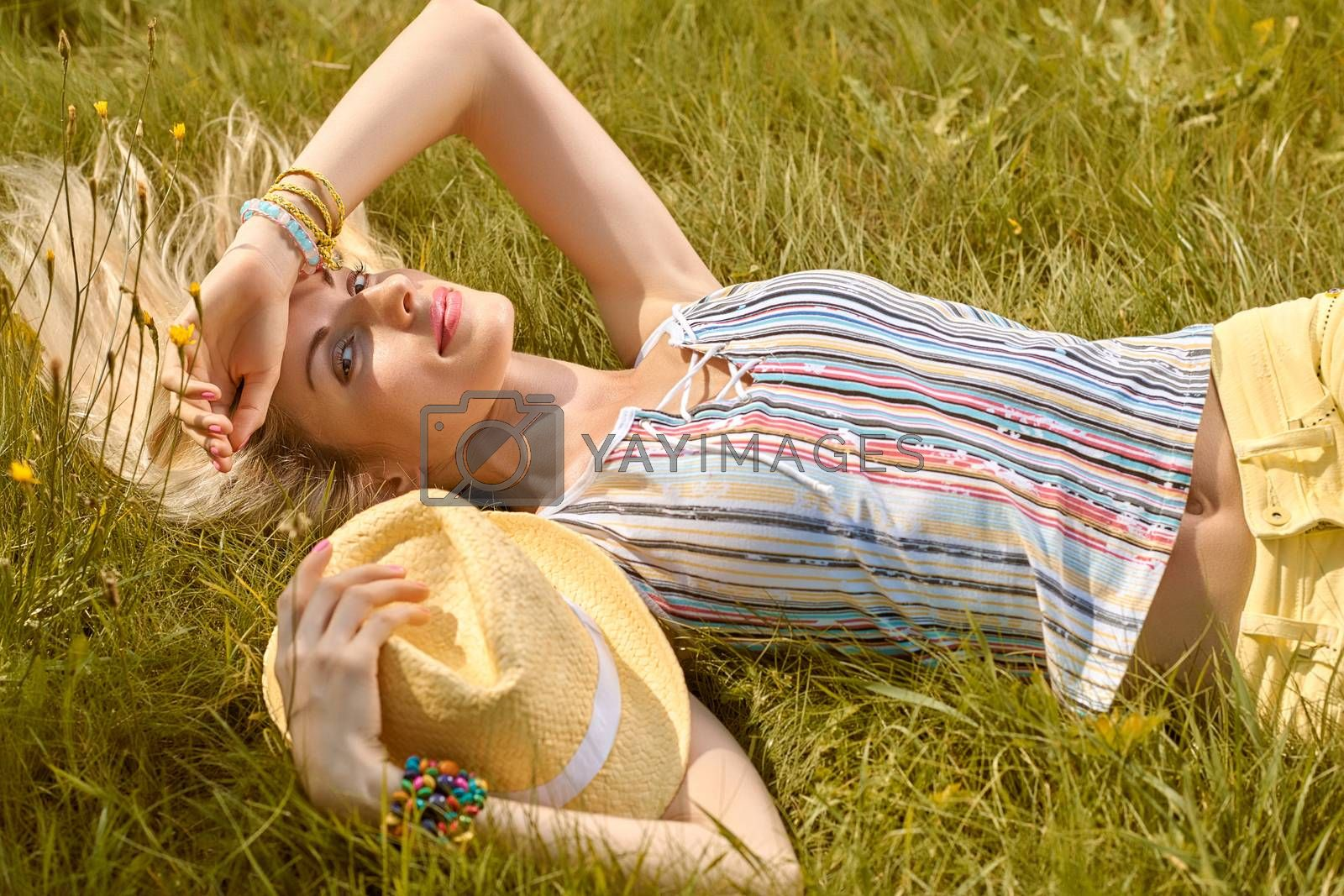 Beauty playful woman relax in summer garden smiling on grass, people, outdoors. Attractive happy blonde girl enjoying nature, harmony on meadow, with hat, lifestyle. Sunny, forest, flowers, copyspace