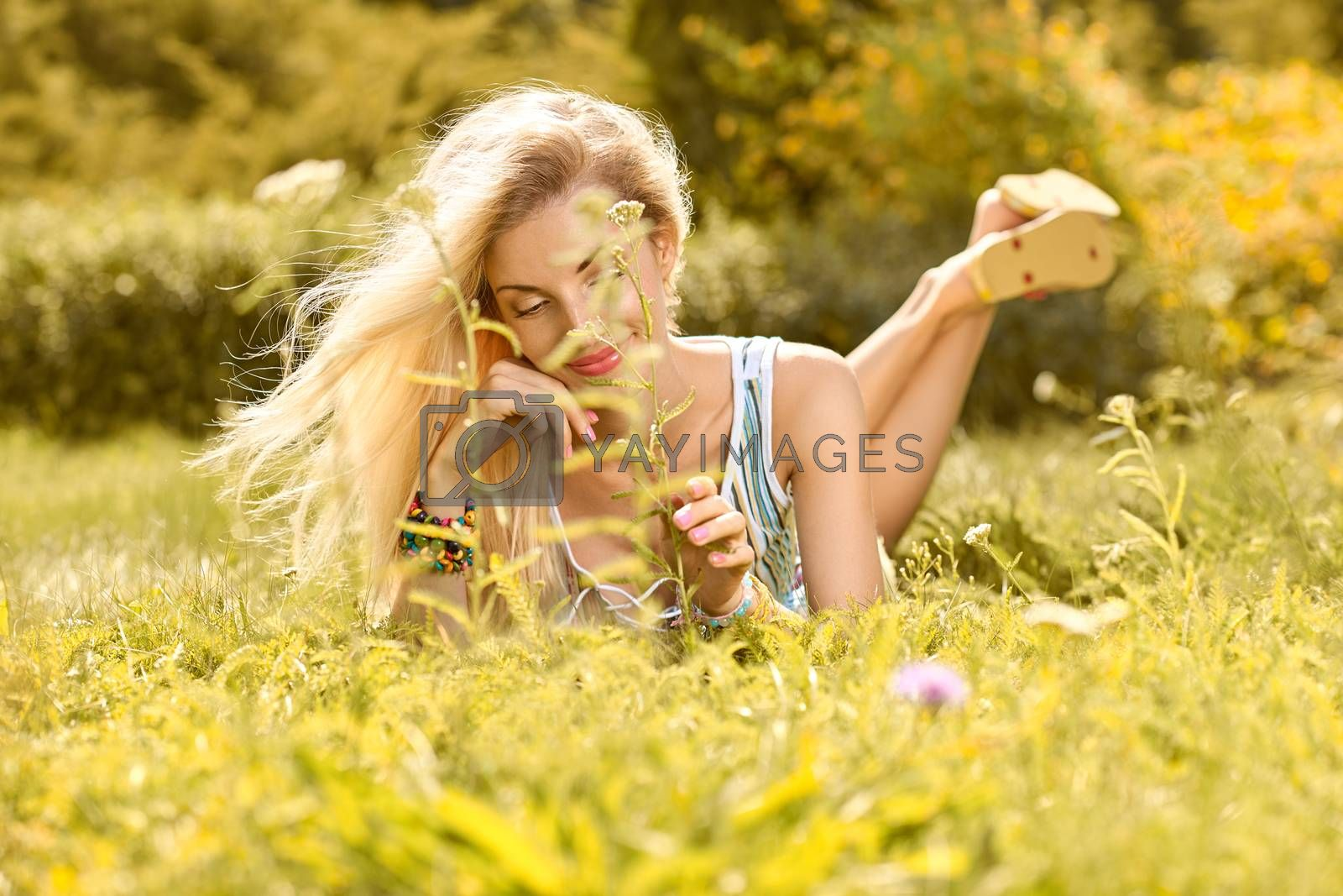 Beauty playful woman relax in summer garden dreaming on grass, people, outdoors, bokeh. Attractive happy blonde girl enjoying nature, harmony on meadow, lifestyle.Sunny day, forest, flowers, copyspace