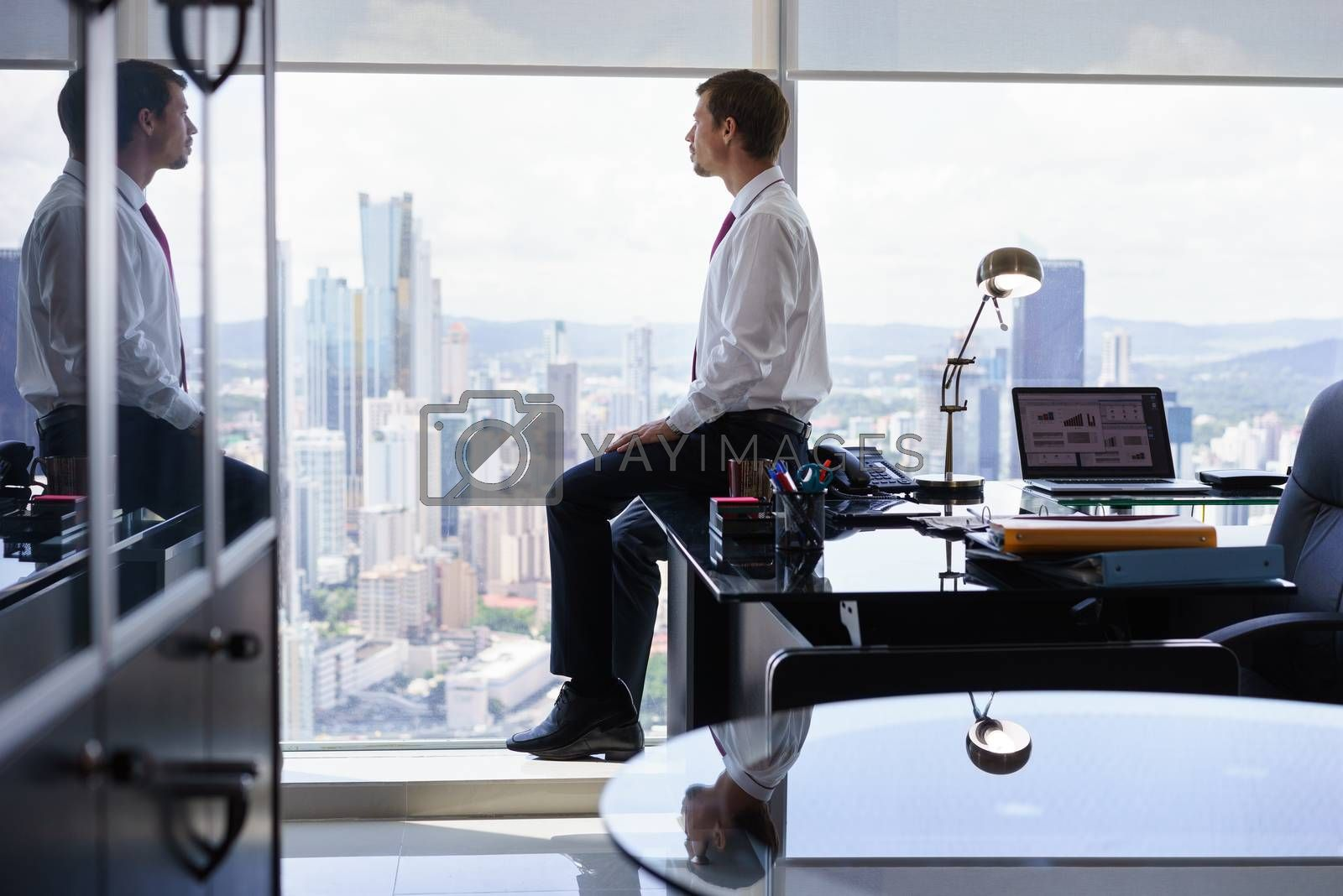 Adult businessman sitting on desk in modern office and looking out of the window, with pensive expression. The man contemplates the city and skyscrapers.