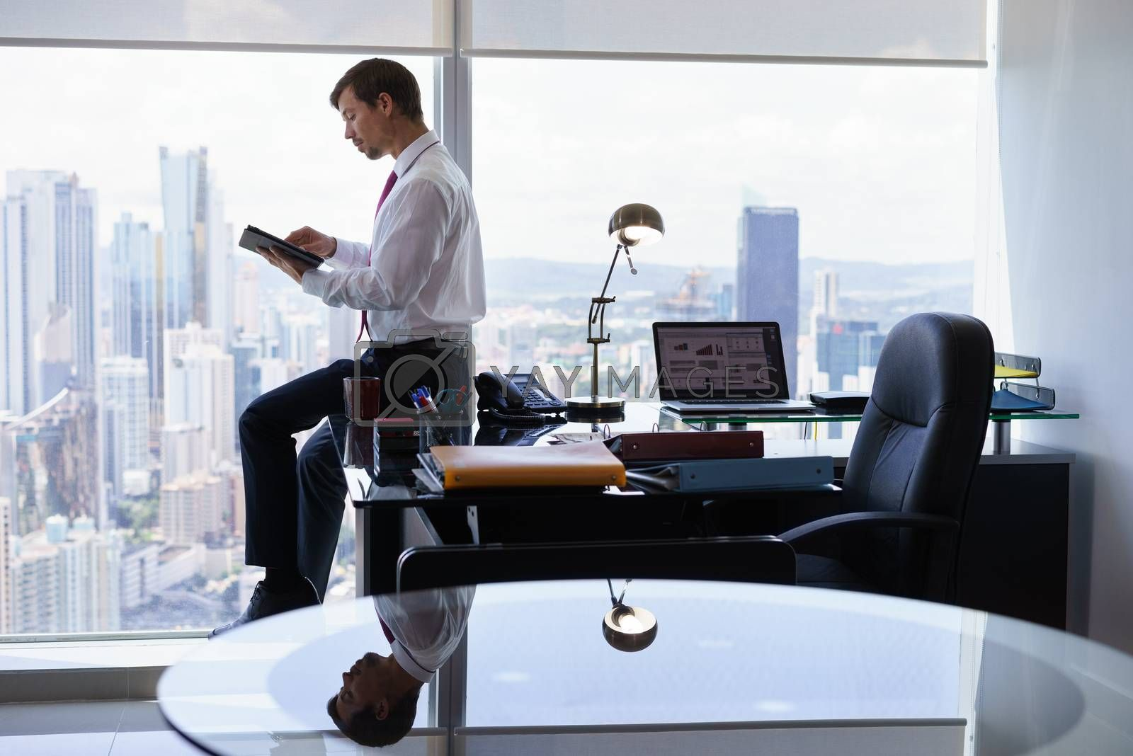 Adult businessman sitting on desk in modern office and reading news on tablet pc. The man works in a skyscraper with a view of the city from the large window.