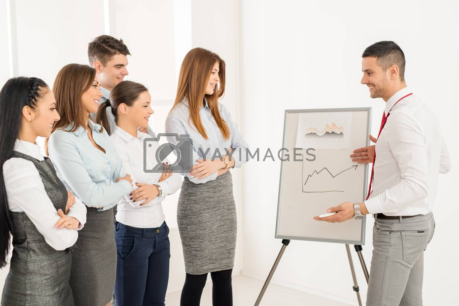 Businesspeople having meeting in a office. Young businessman standing  in front of flip chart and having presentation.