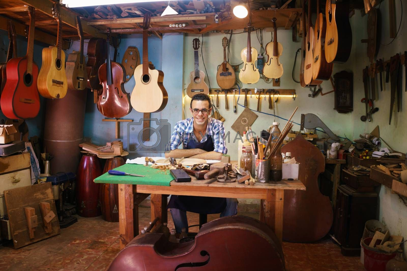 Lute maker shop and acoustic music instruments: portrait of a young adult artisan sitting at his desk and smiling at camera. He is surrounded by many guitars, mandolins and violins.