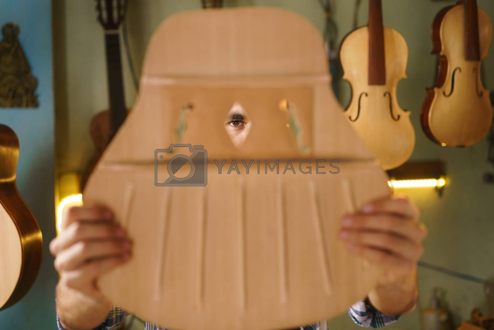 Lute maker shop and acoustic music instruments: young adult artisan carving and chiseling the body of a classic guitar. He is examining the design of the holes in the wooden body.