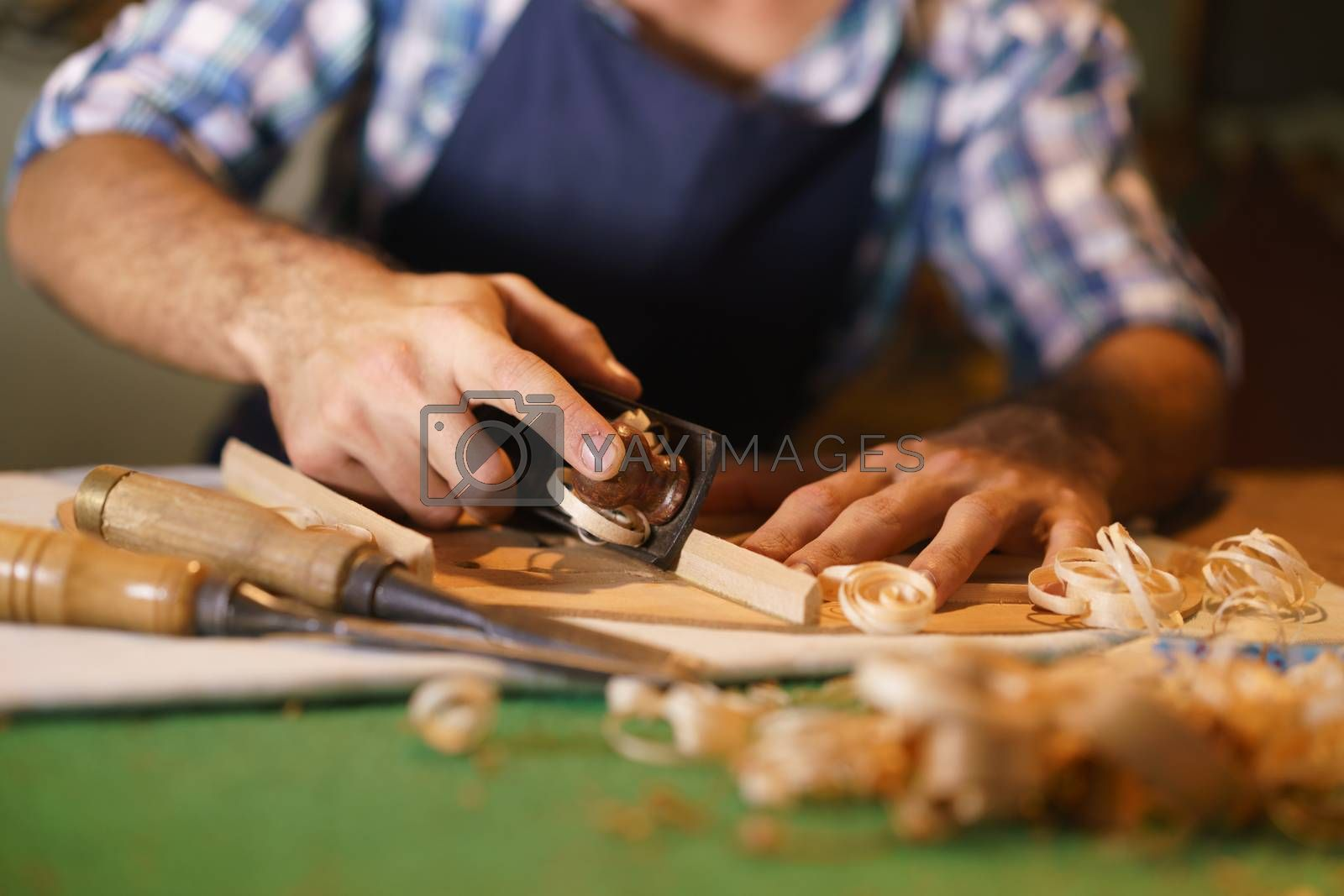 Lute maker shop and acoustic music instruments: young adult artisan cutting and chiseling wood to make a classic guitar. Closeup of his hand using a tool on guitar body