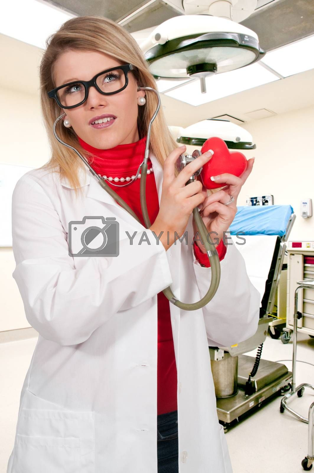 Beautiful young woman cardiologist doctor holding a heart
