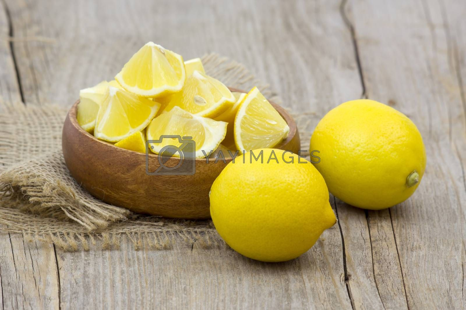 fresh lemons in a bowl on wooden background by miradrozdowski