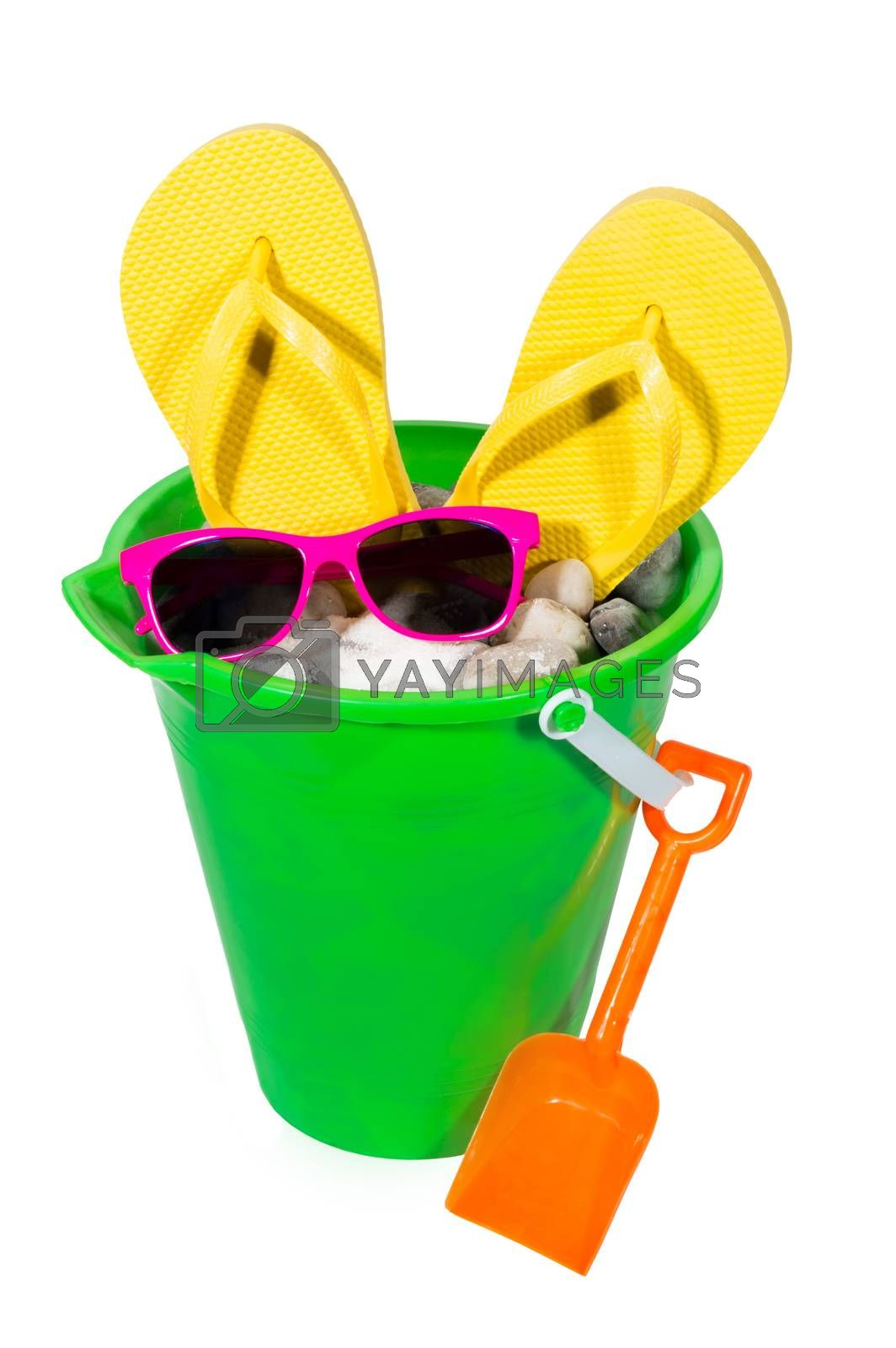 Vertical isolated shot of brightly colored green pail with shovel, yellow flip flops and sunglasses