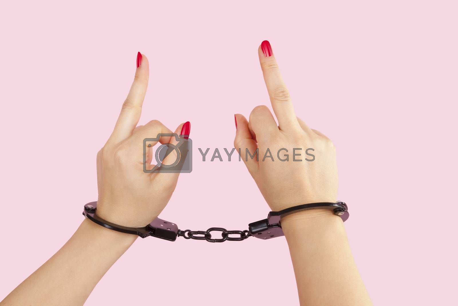 Beautiful female hands in black handcuffs showing the middle finger isolated on pink background. Submission, trust and passion concept.