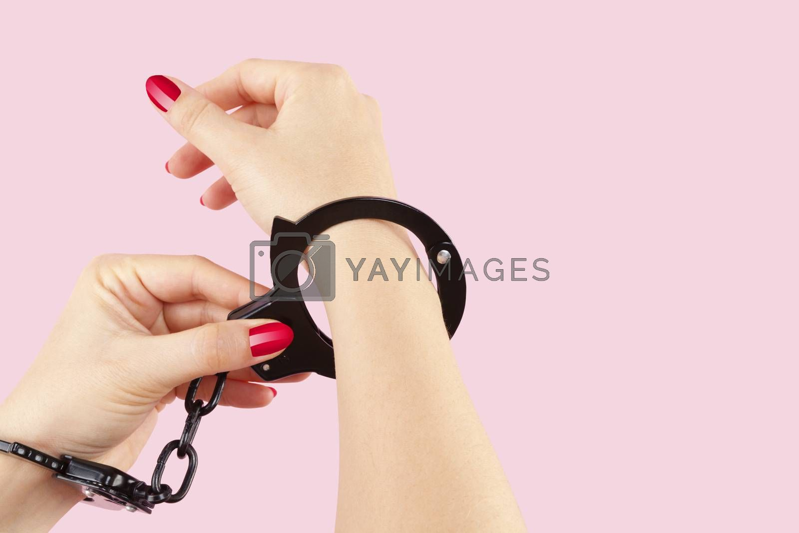 Beautiful female hands in black handcuffs isolated on pink background. Submission, trust and passion concept.