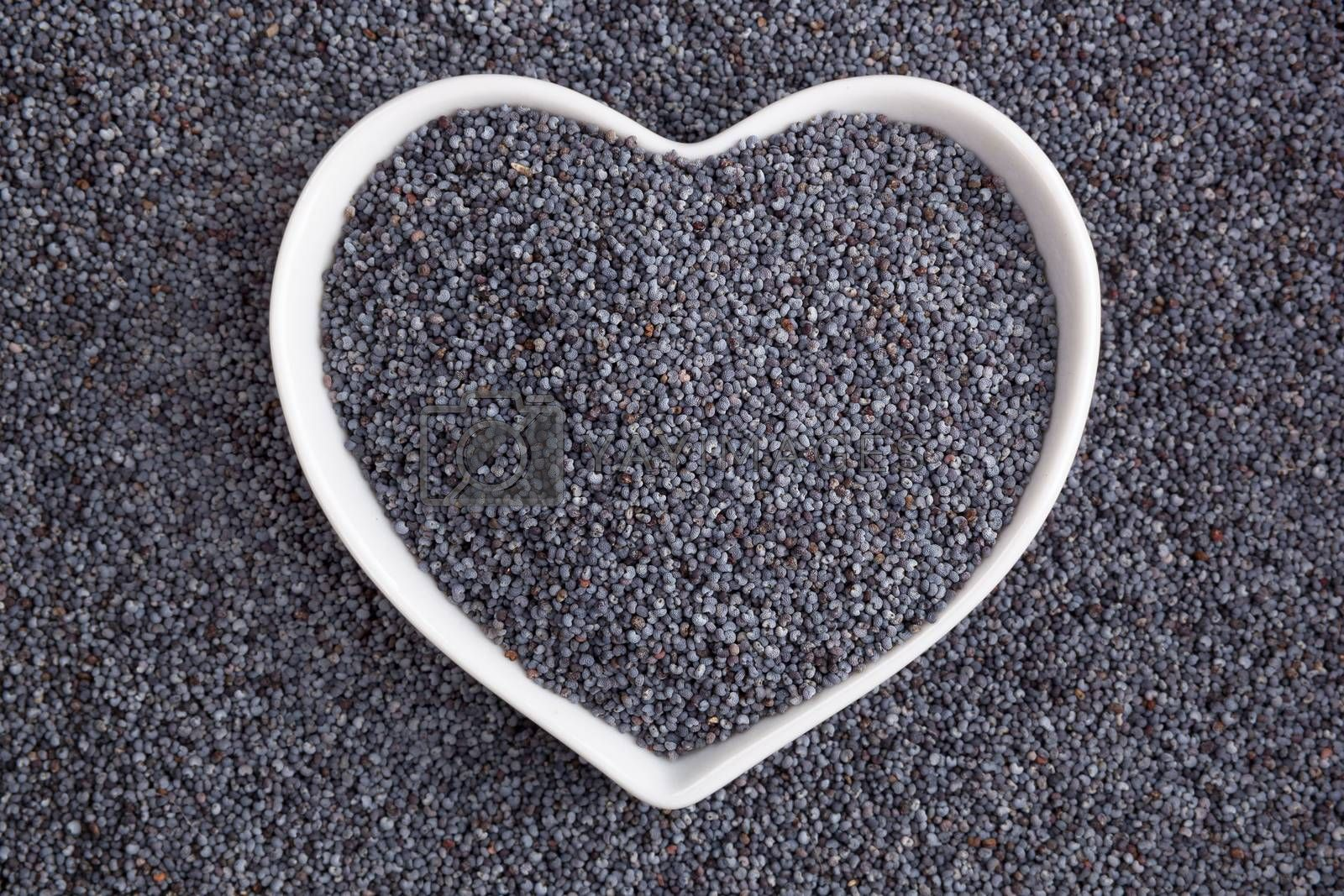 Poppy seed background. Poppy seeds in heart shaped bowl, top view. Healthy eating.