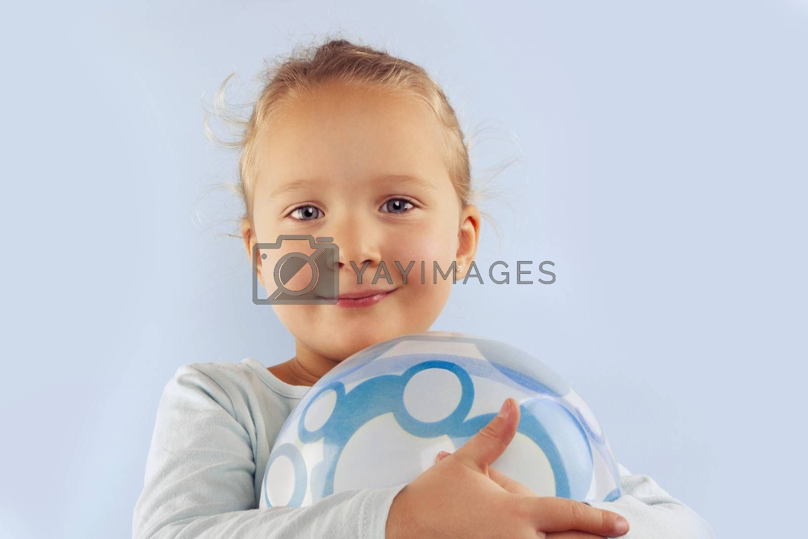 Summer. Adorable beautiful girl with ball against blue background. Summer background.