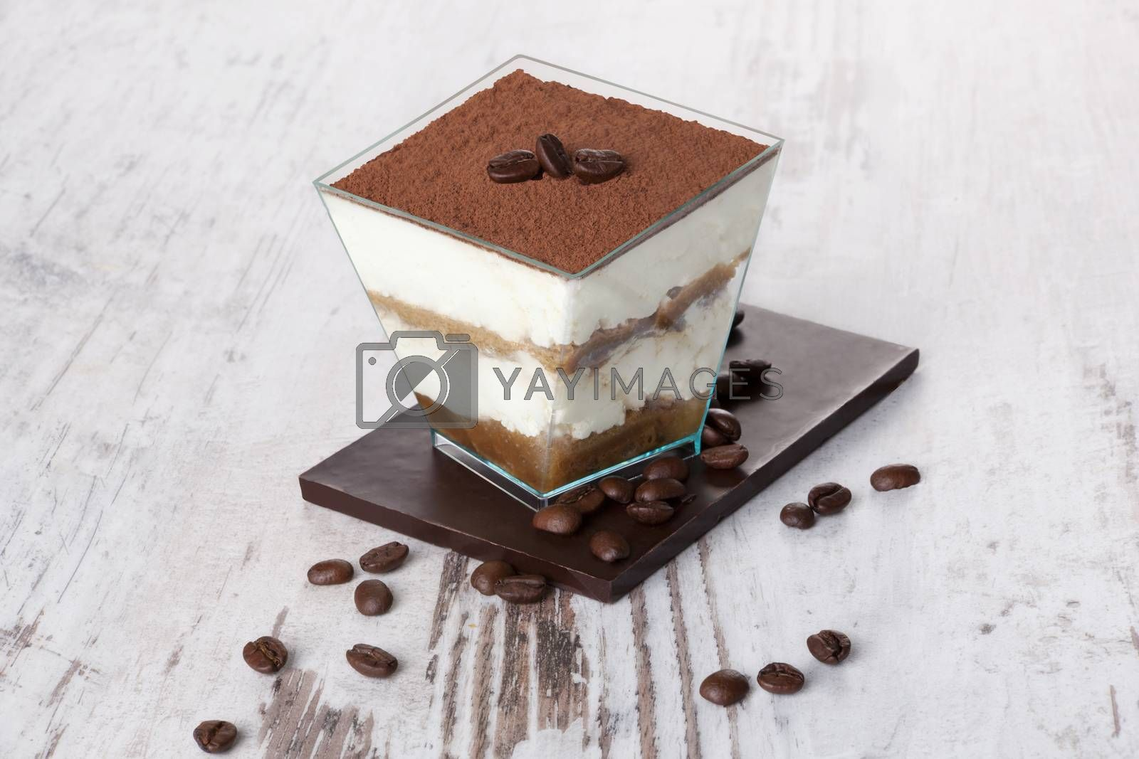 Tiramisu dessert with chocolate and coffee beans on white wooden textured table. Traditional tiramisu dessert, rustic, country style.