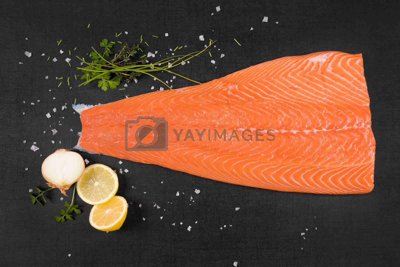 Fresh raw salmon background. Salmon steak, lemon, rosemary and parsley leaf and salt on black background, flat lay.