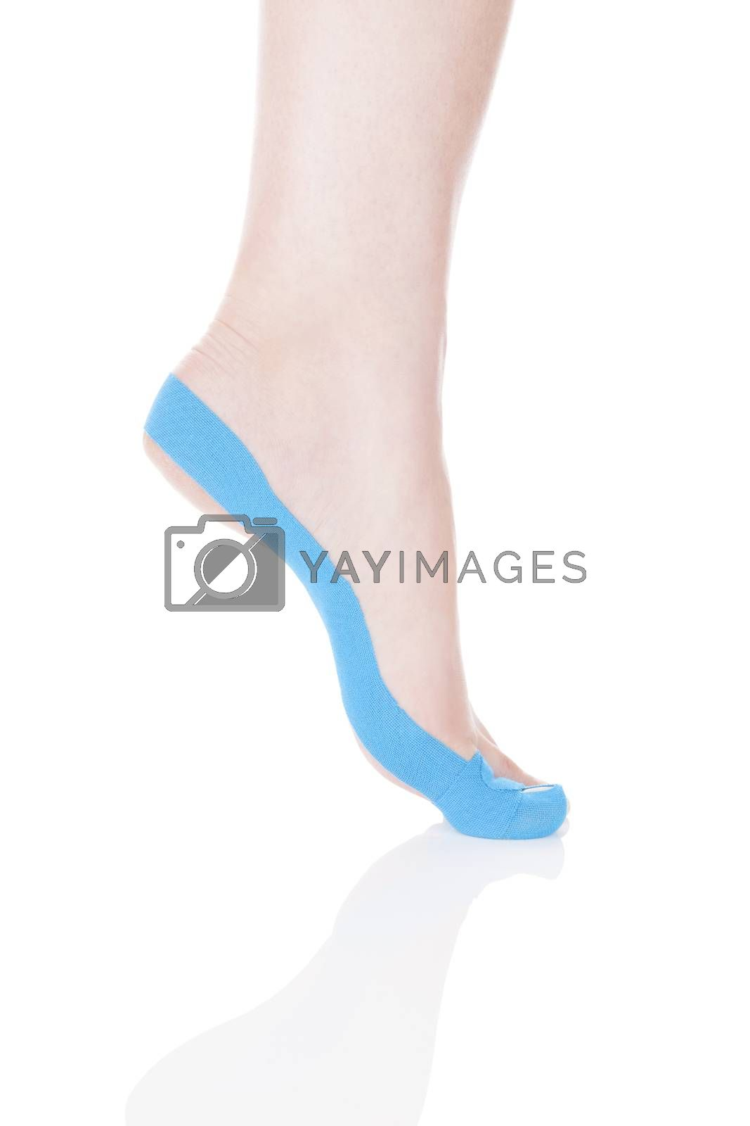 Therapeutic tape on female foot isolated on white background. Chronic pain, alternative medicine. Rehabilitation and physiotherapy.