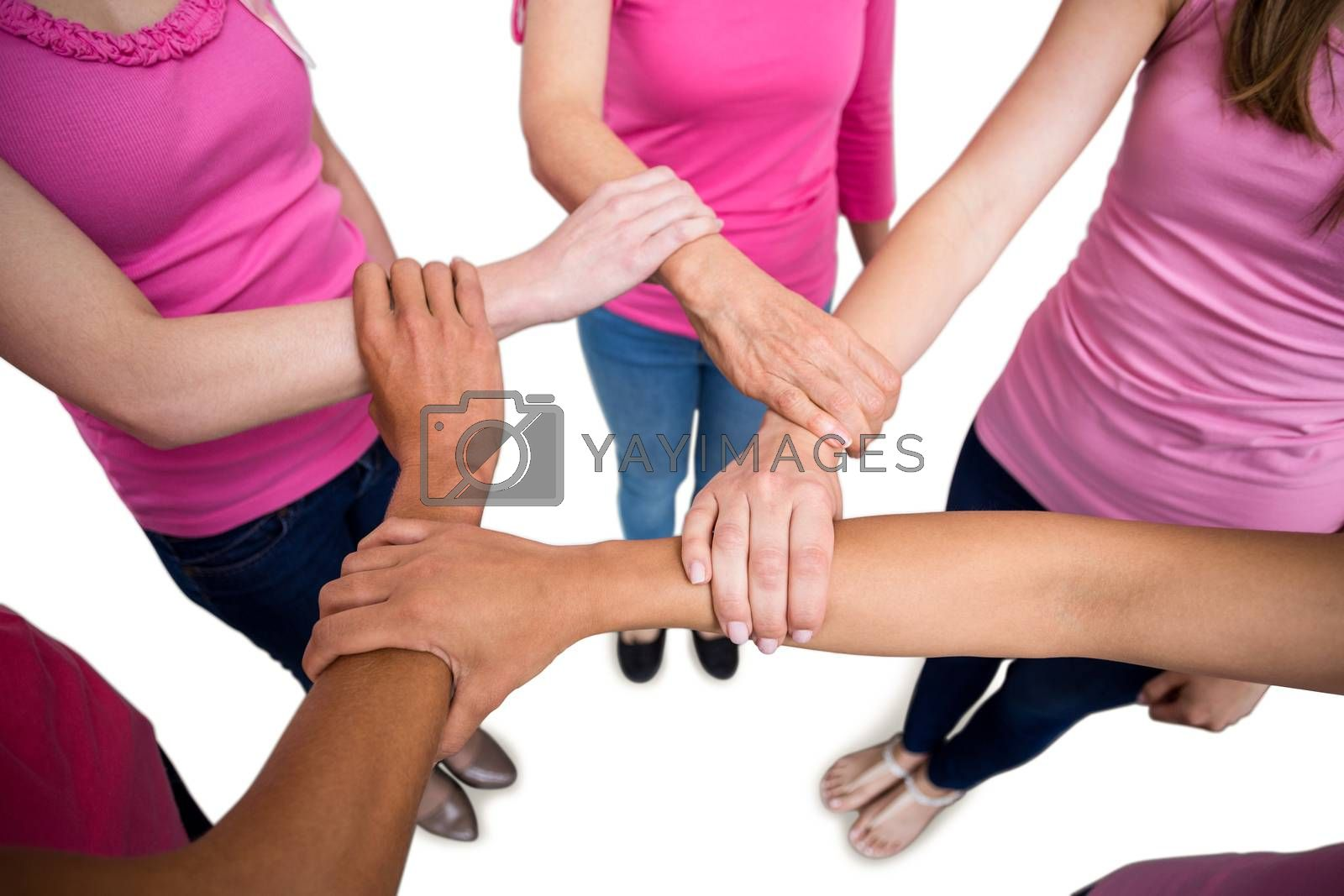 Royalty free image of Women in pink outfits joining in a circle for breast cancer awareness by Wavebreakmedia